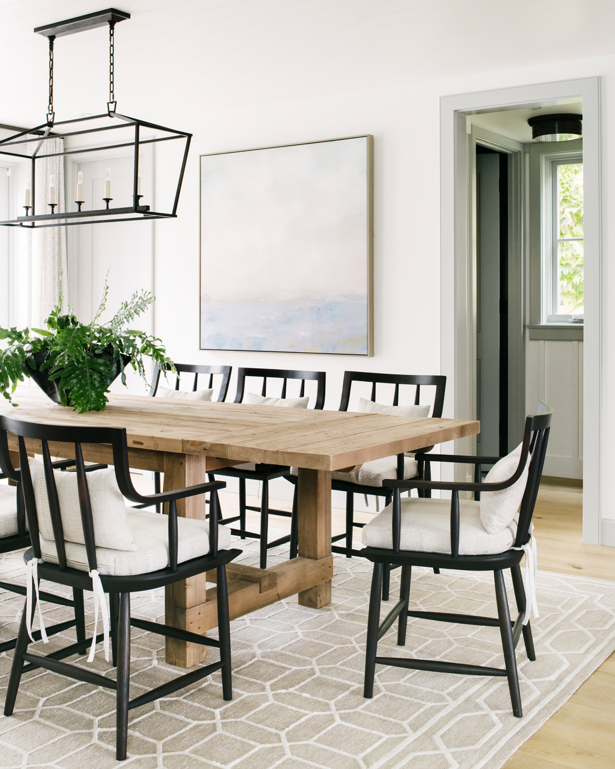unfinished wooden dining table with black wooden chairs and cream colored cushions