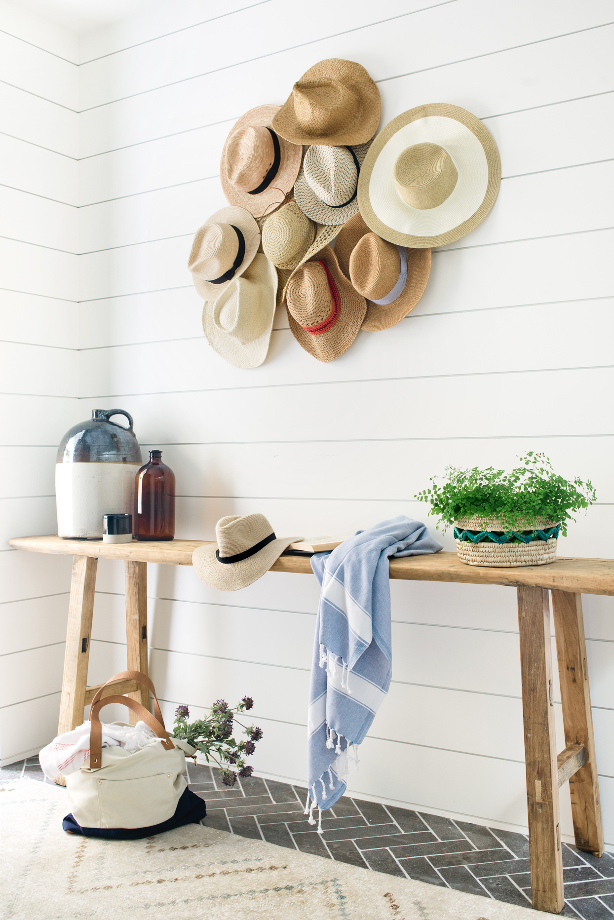 various hats hung on entryway wall with wooden table beneath