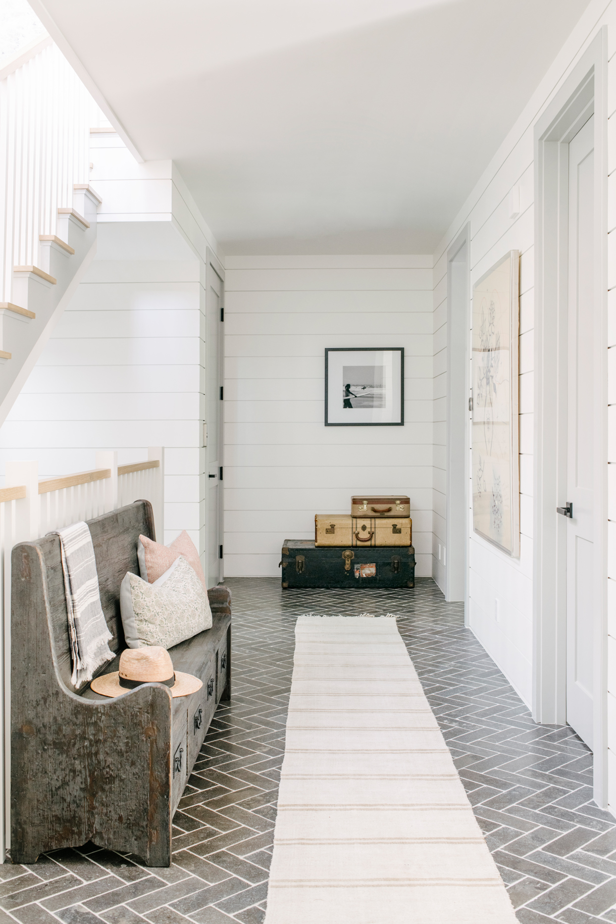 herringbone pattern limestone brick flooring with long cream and white runner