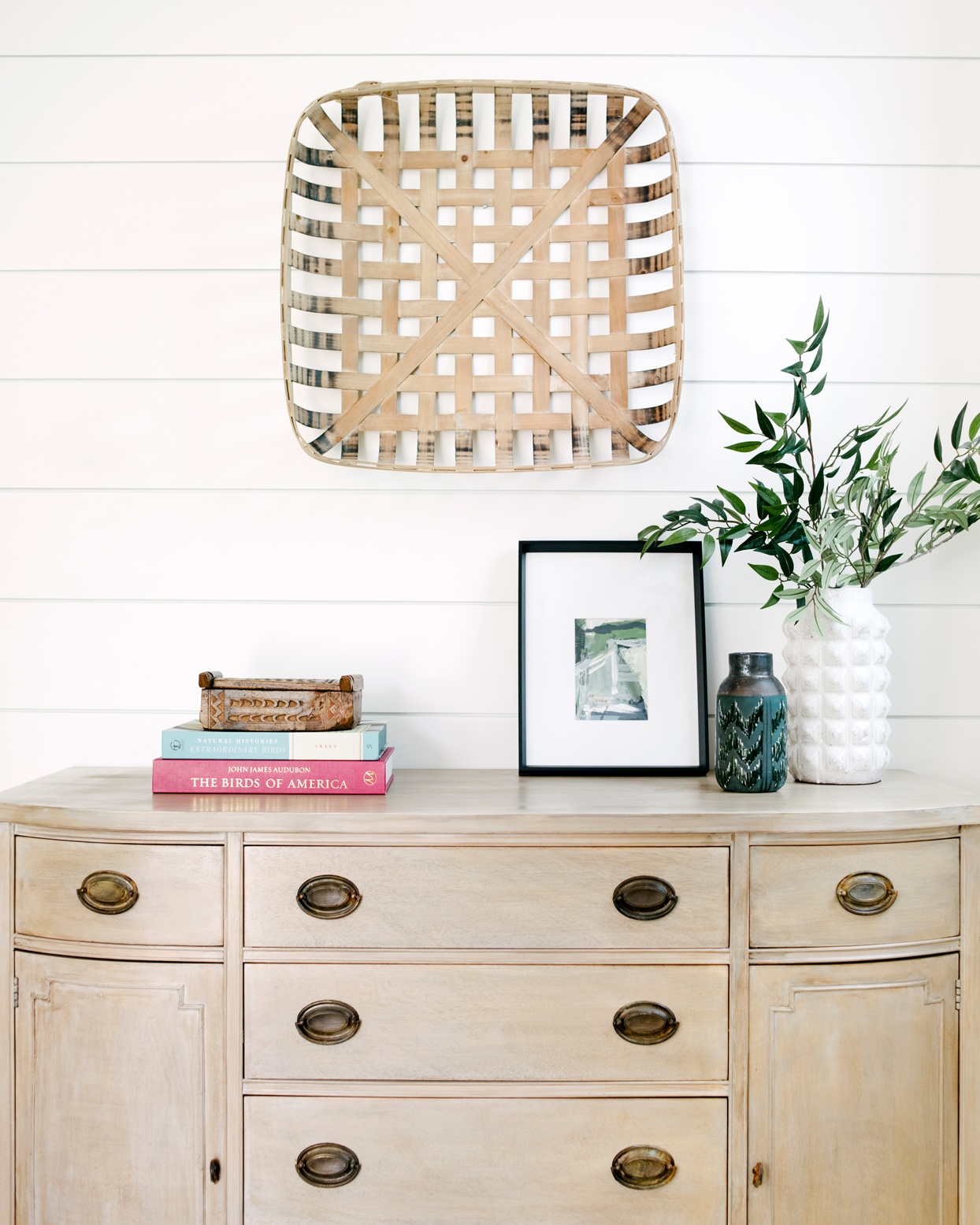 light brown cabinet with woven basket wall decor