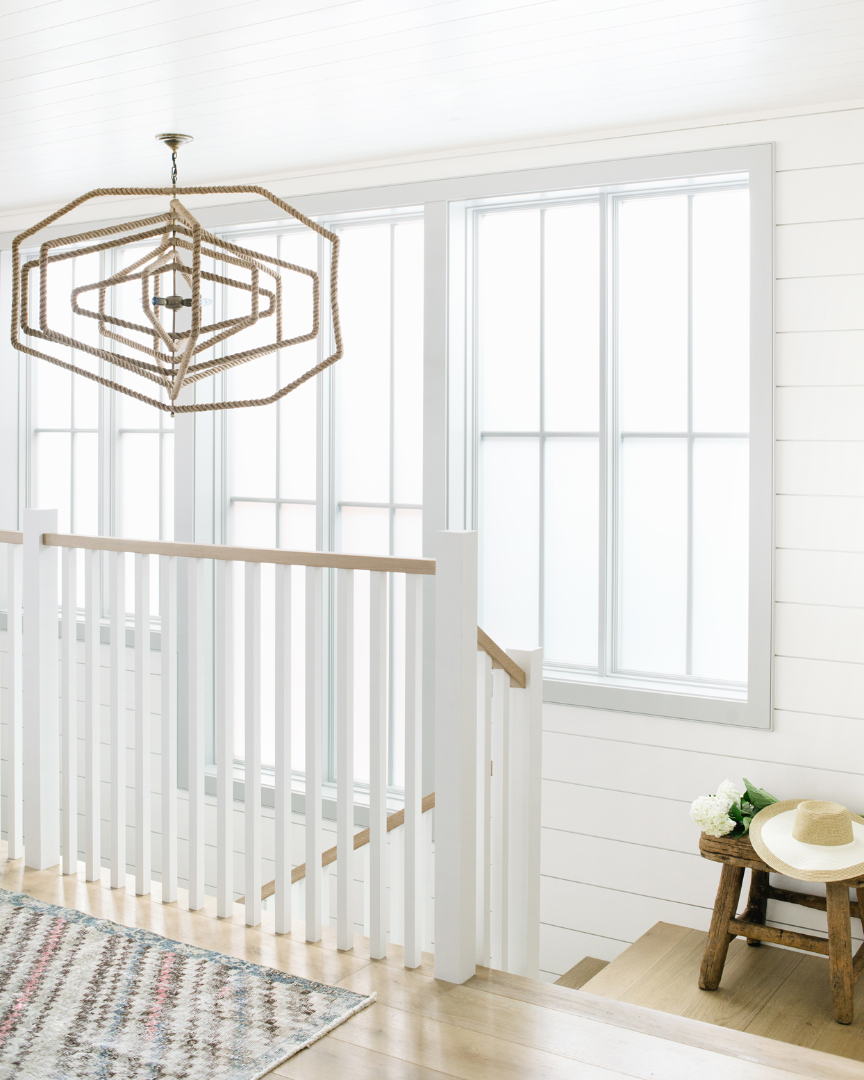 white railing stairway area large windows