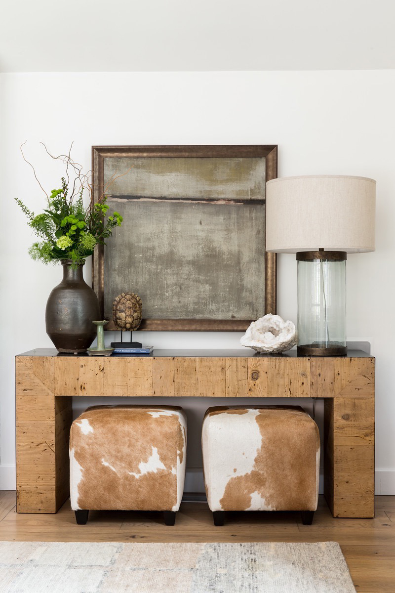 gray and honey colored entry way with cow skin ottomans