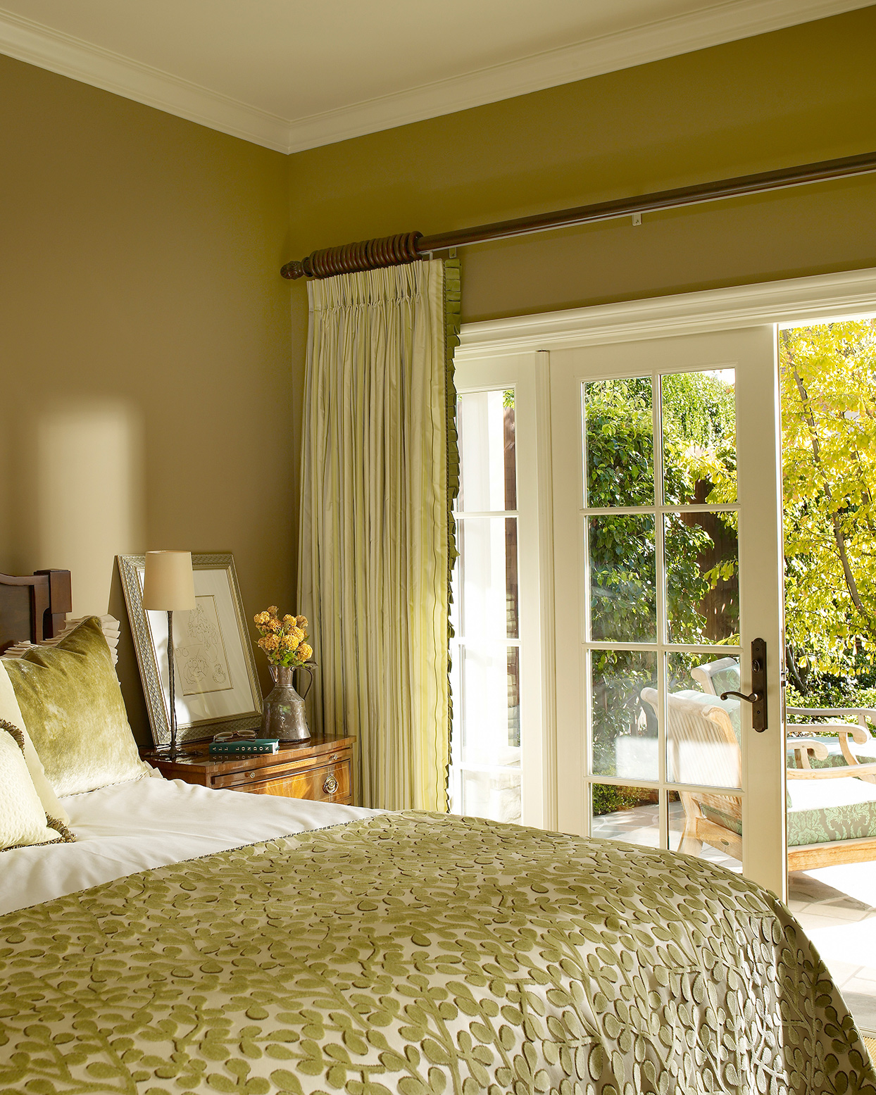 yellow-green toned bedroom with french doors opening to sunny patio