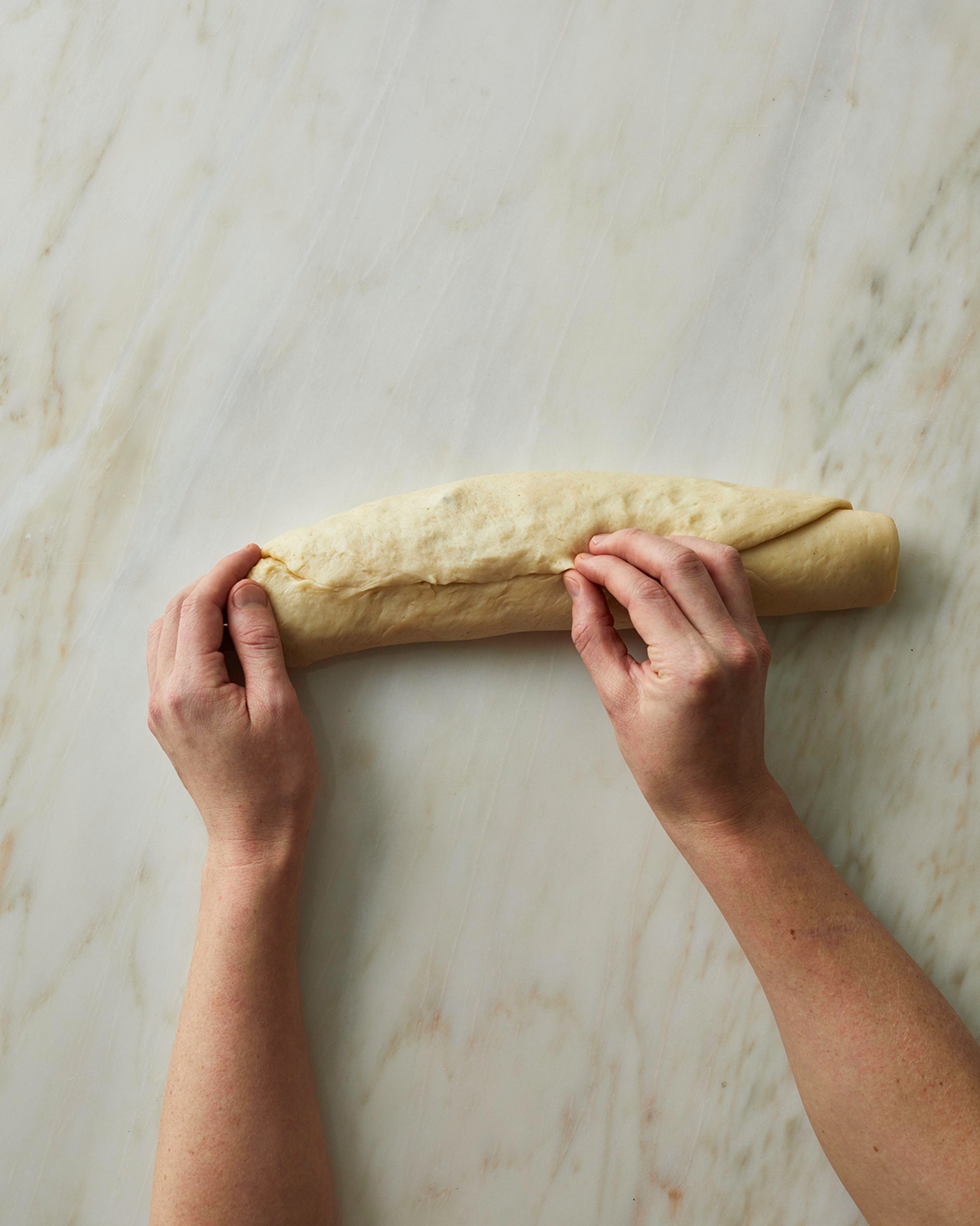 Pinching the seam on rolled swirl bread dough