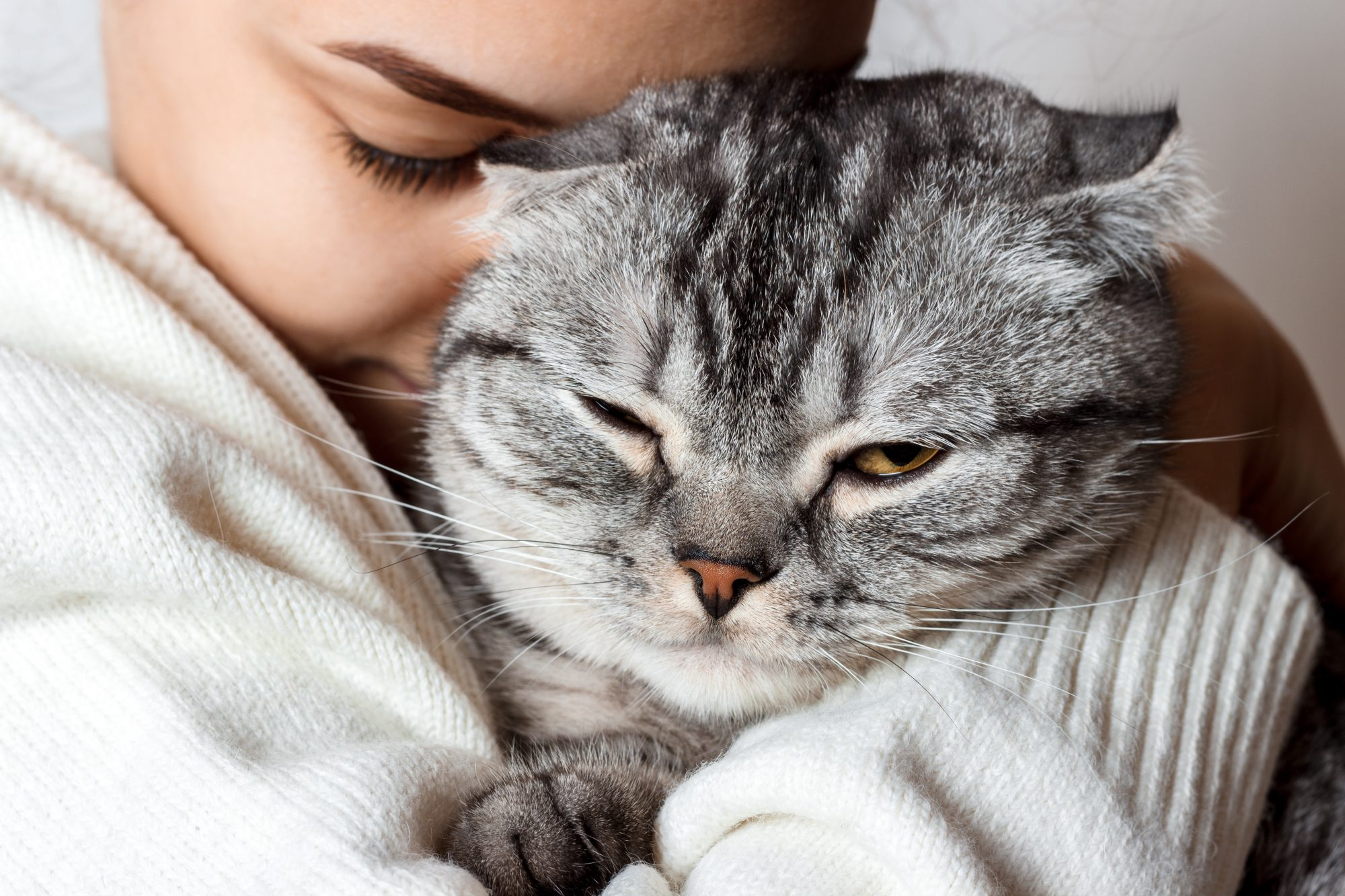 a smiling woman snuggling her cat