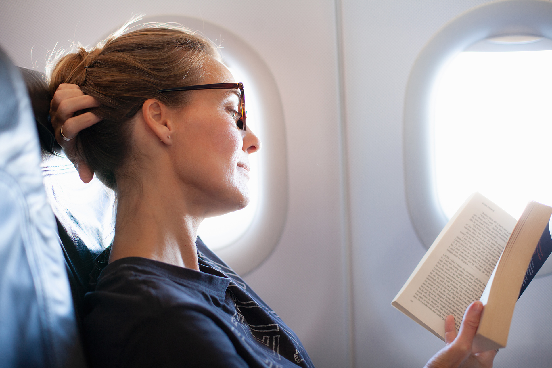 women in airplane seat reading book