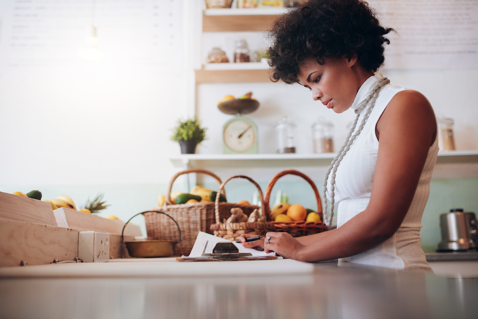 woman at kitchen counter writing on paper