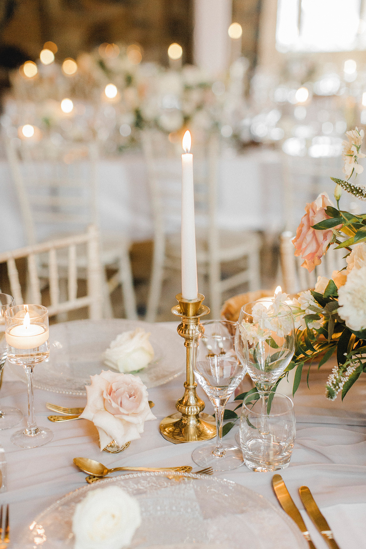 elegant candles and golden decor on wedding reception tables