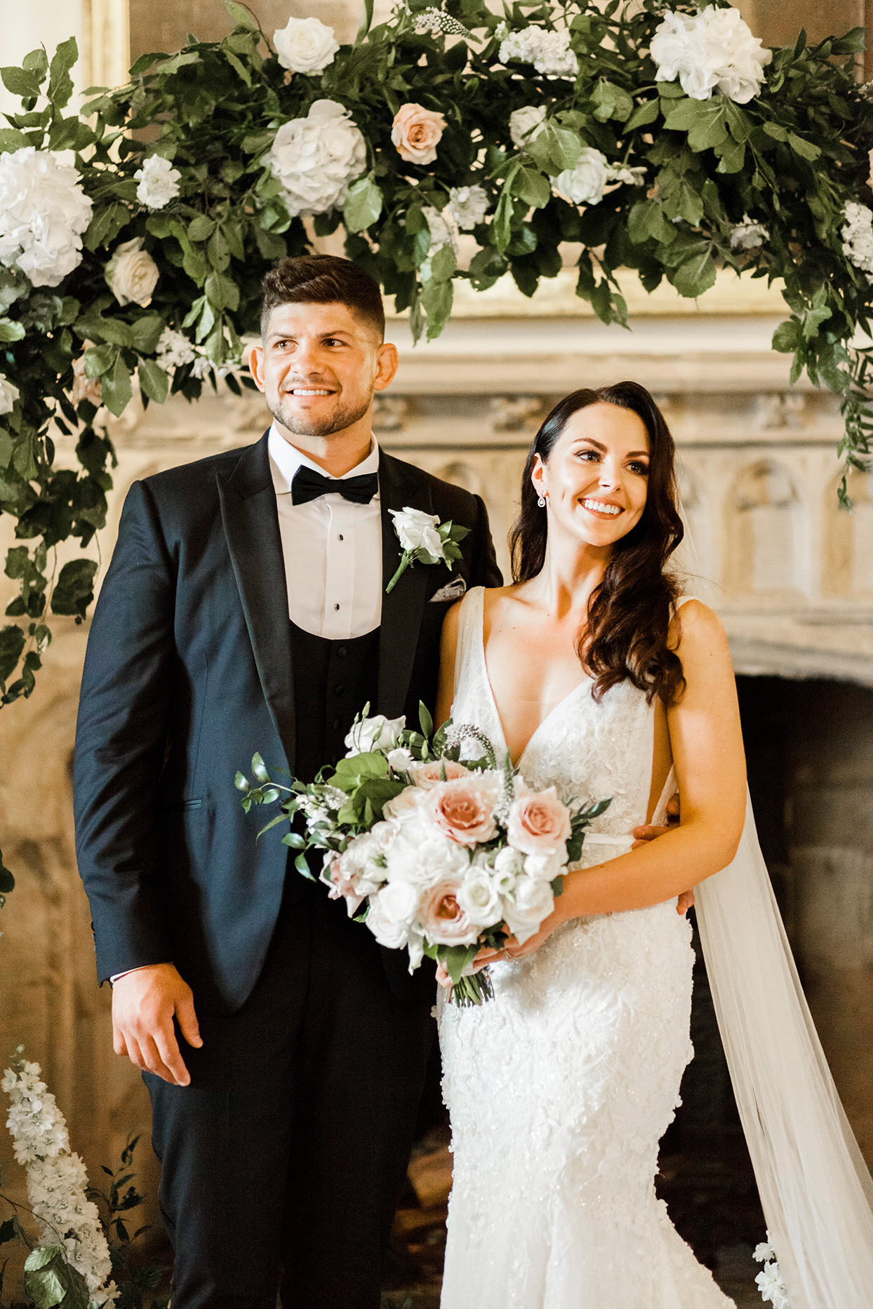 bride and groom portrait in front of castle fireplace under floral arch