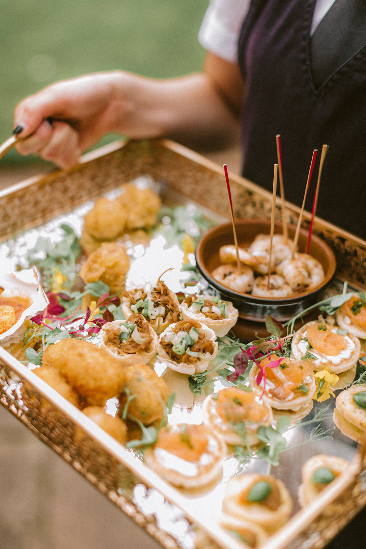 appetizer food on ornate tray in server's hands
