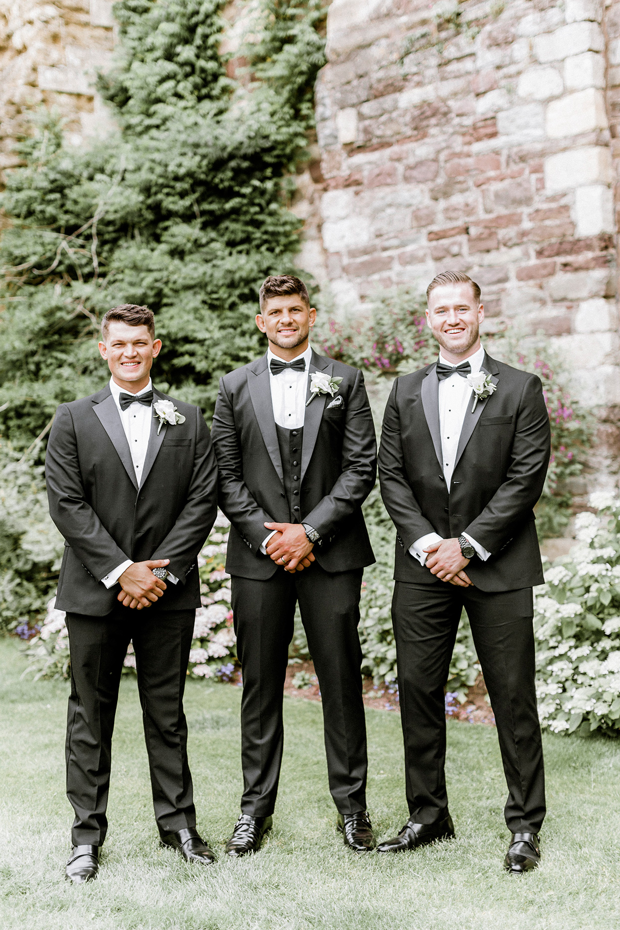 groom and groomsmen standing together in black suits on lawn
