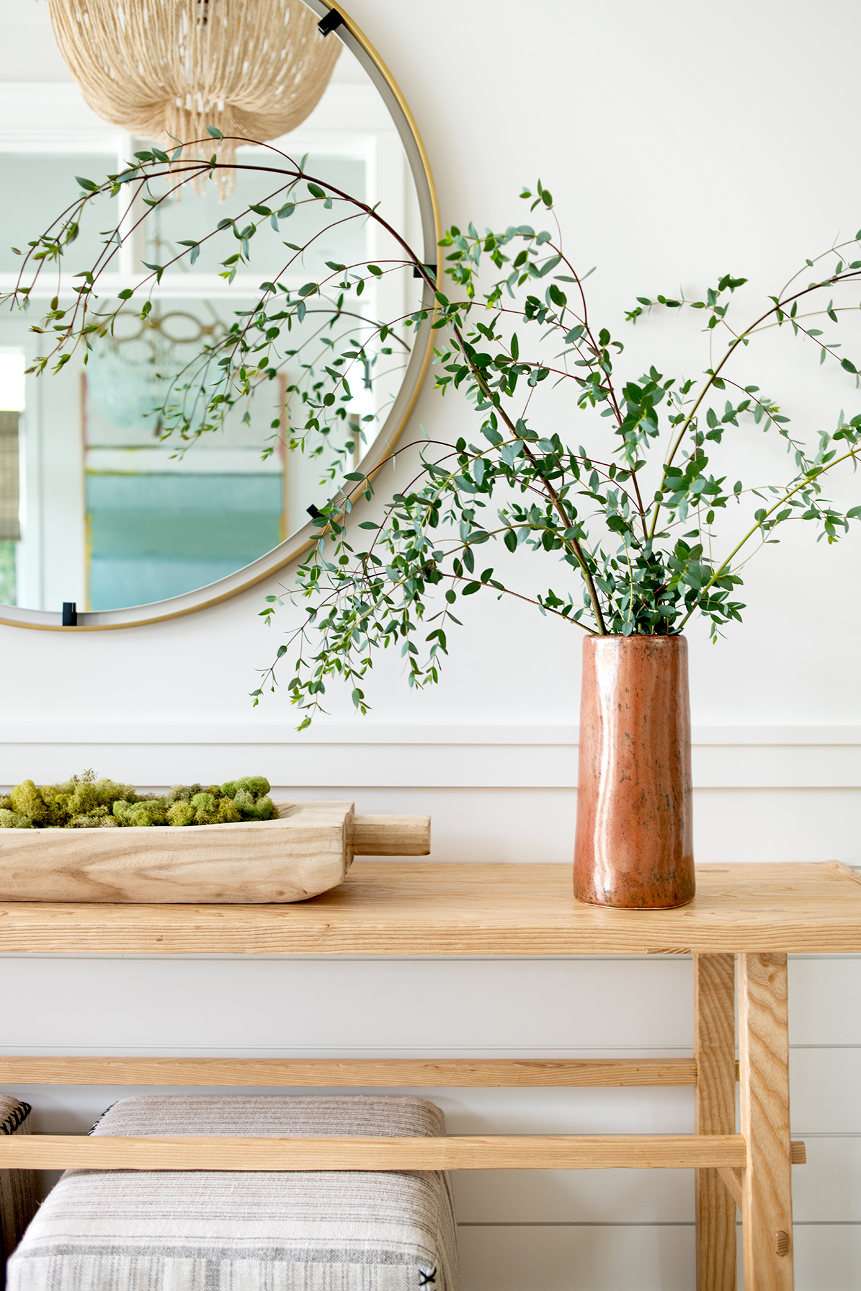 circular mirror with green plant in vase on table