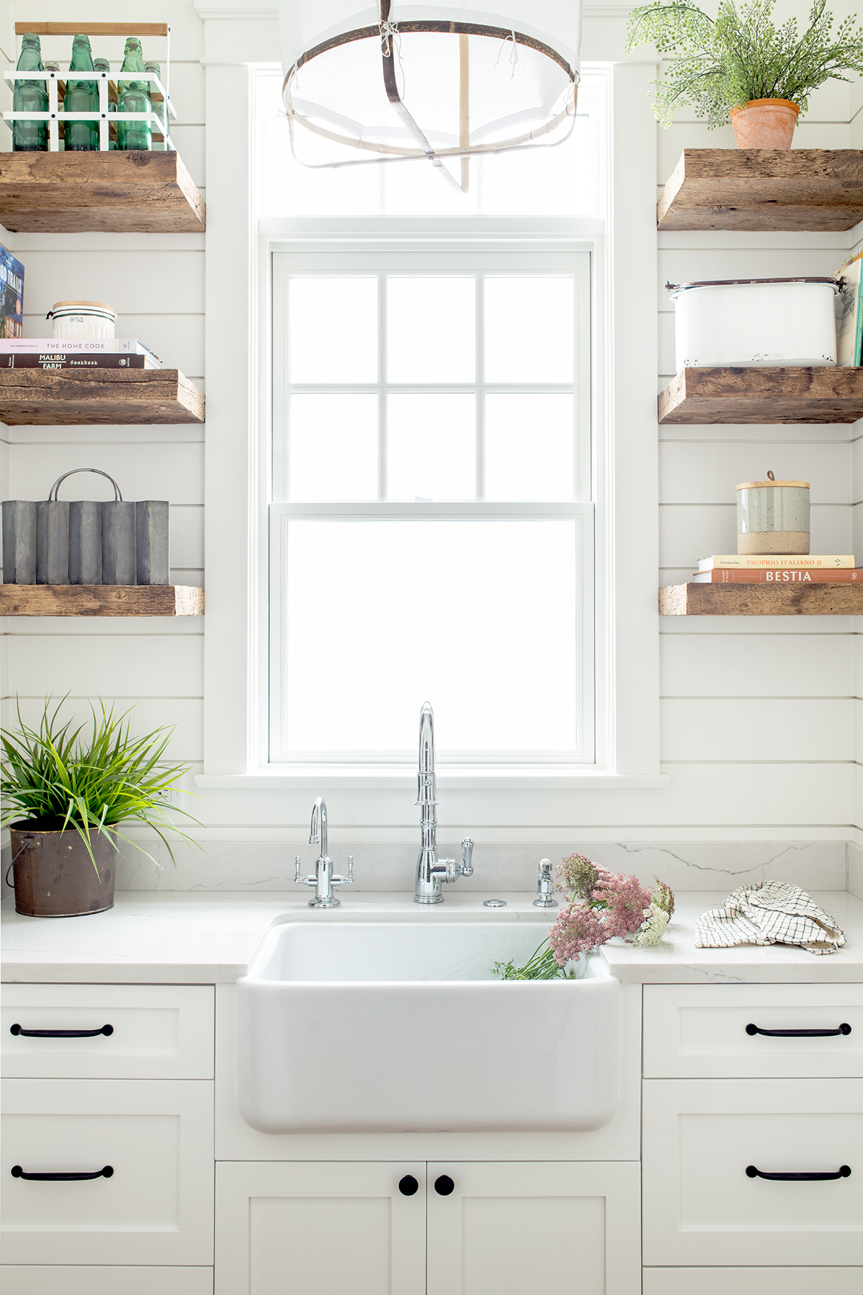 white kitchen sink area with rustic wooden shelves