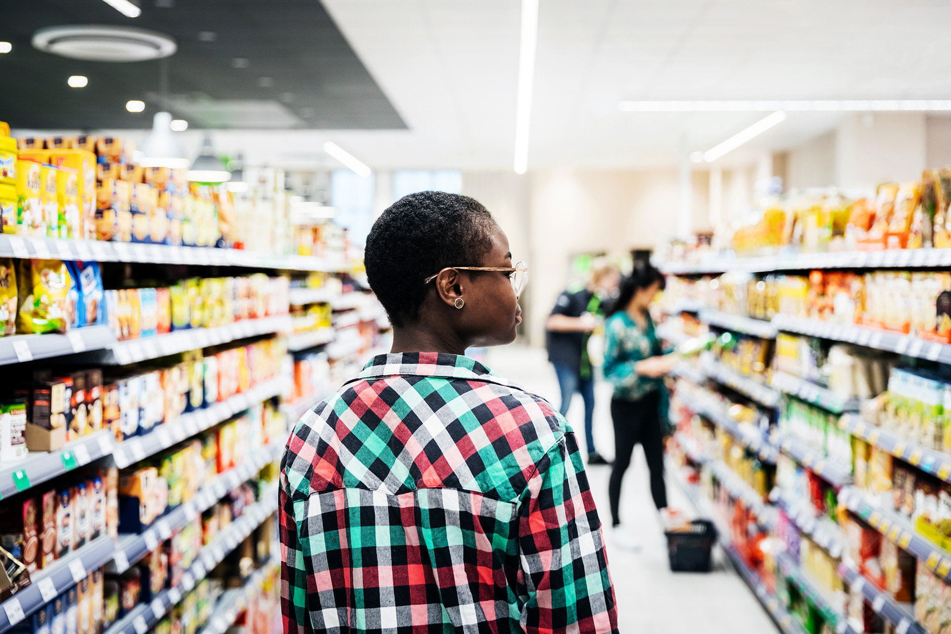 Young Woman Walking Down Supermarket Aisle