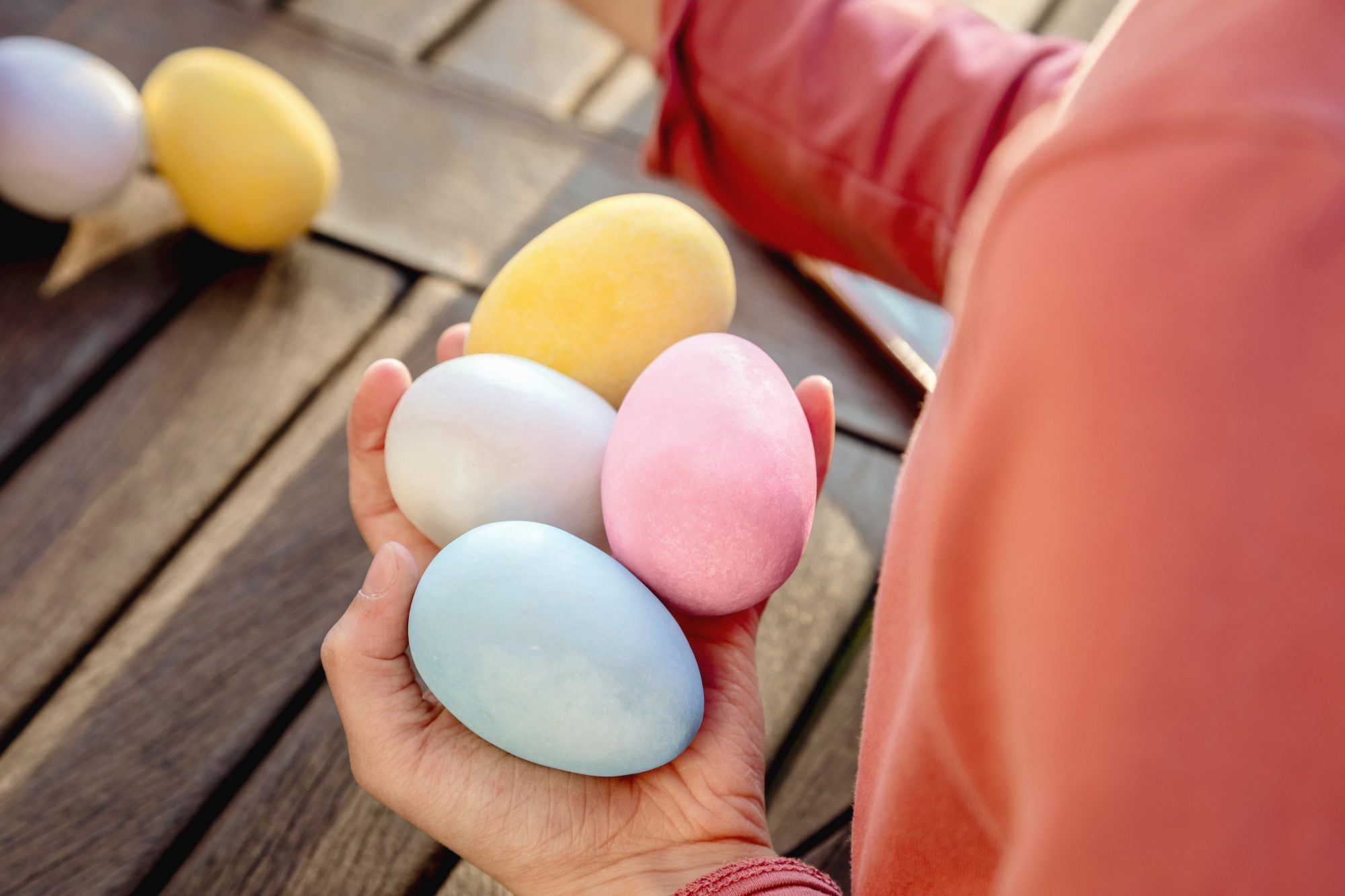Girl with a handful of dyed Easter eggs at table, cropped over shoulder view