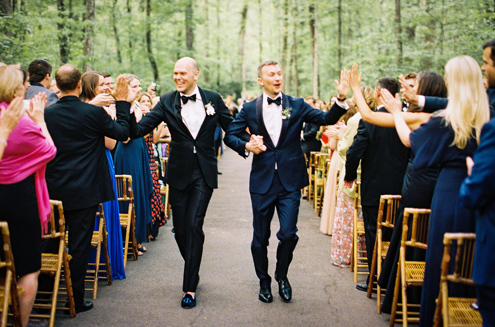 grooms recessing after ceremony and giving guests high fives