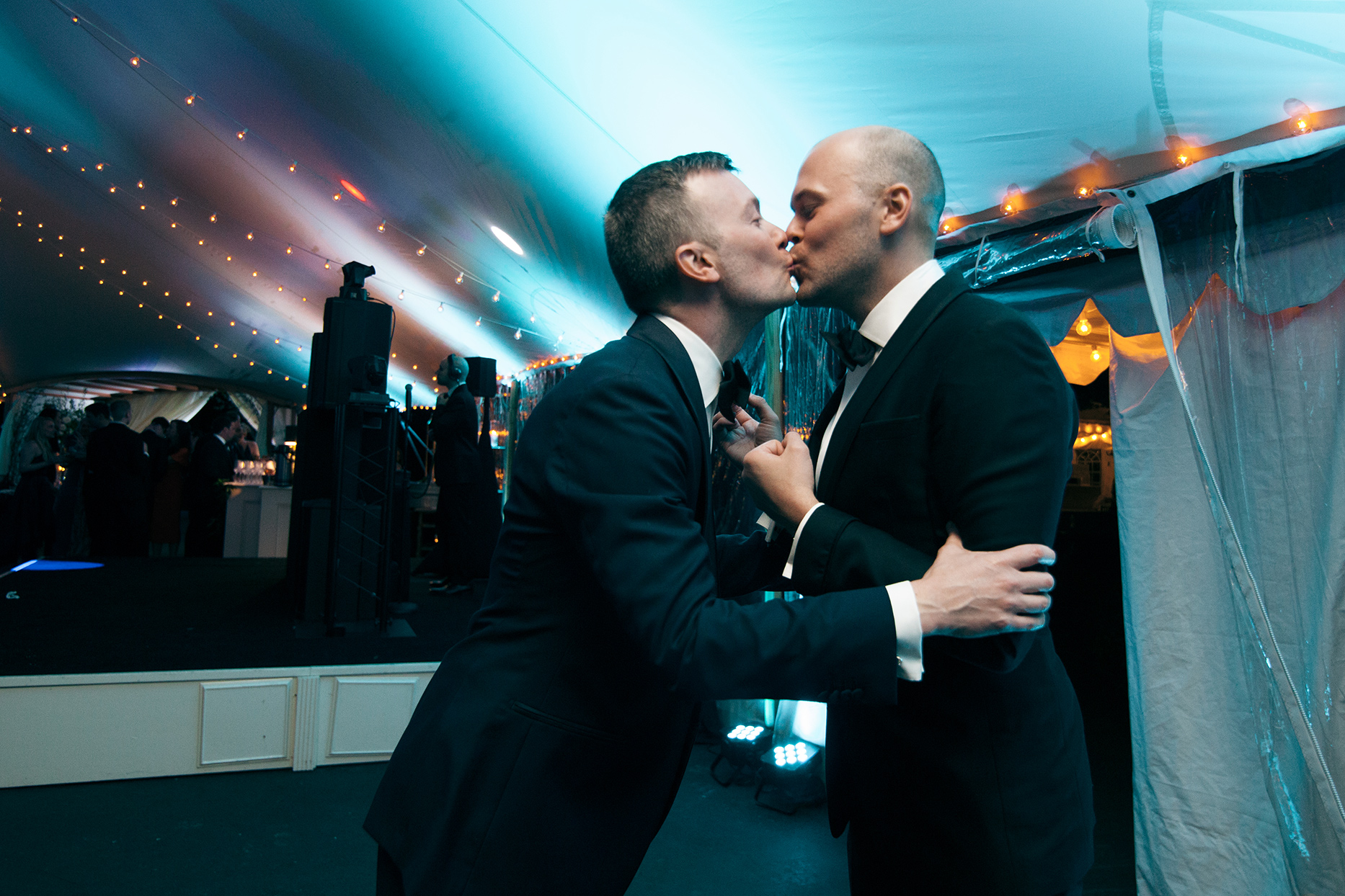 grooms kissing in colorfully lit party tent