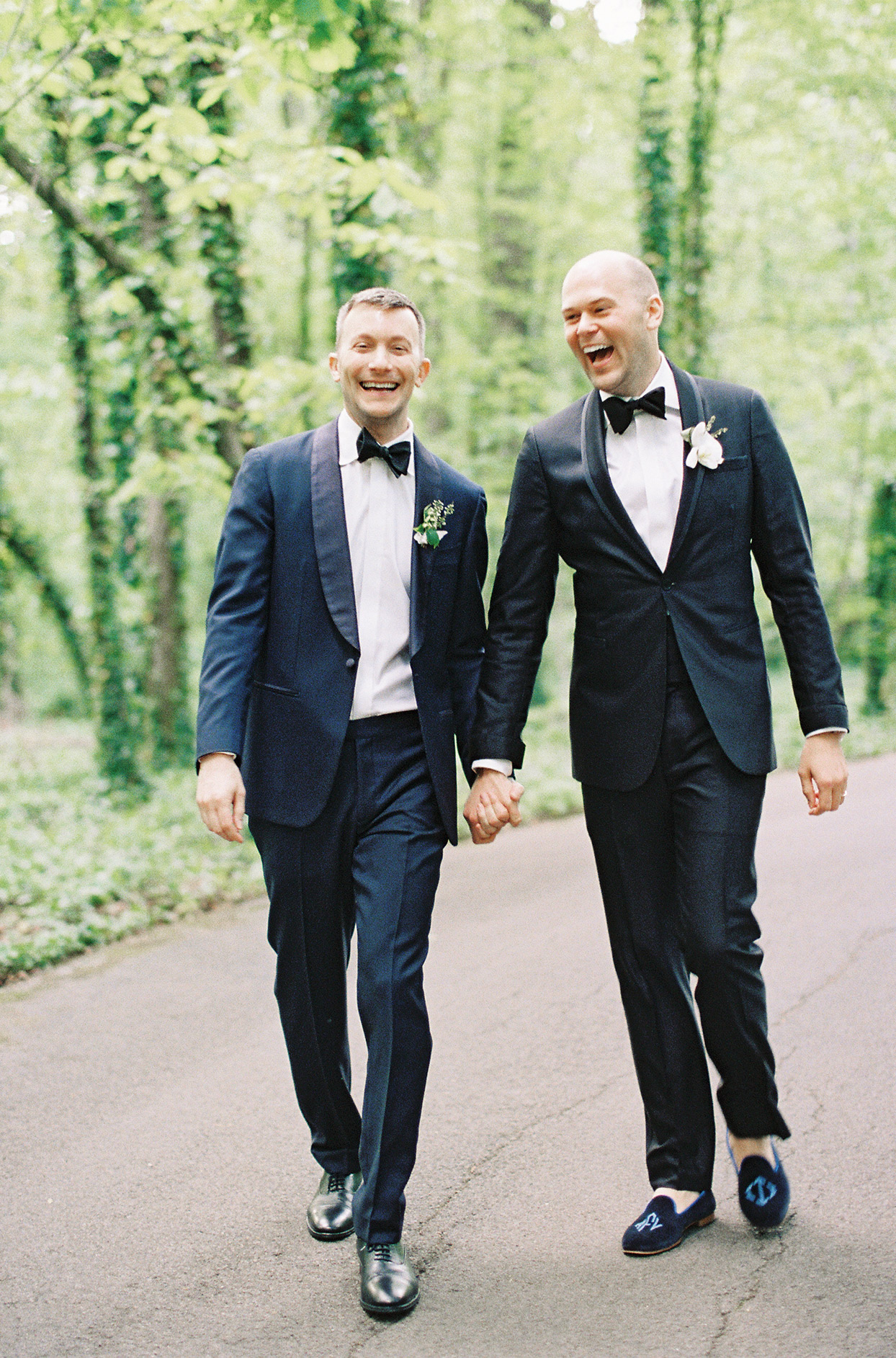 grooms holding hands walking through forest