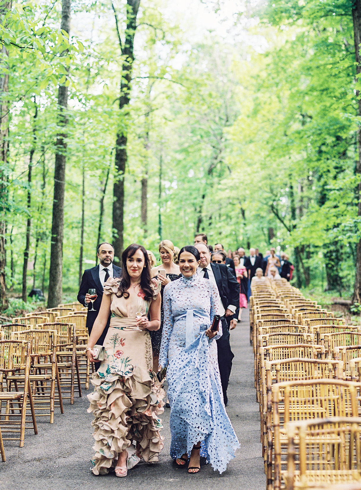 wedding guests walking up ceremony aisle