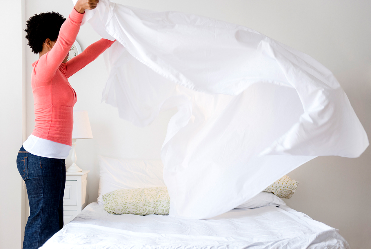 woman putting on sheets