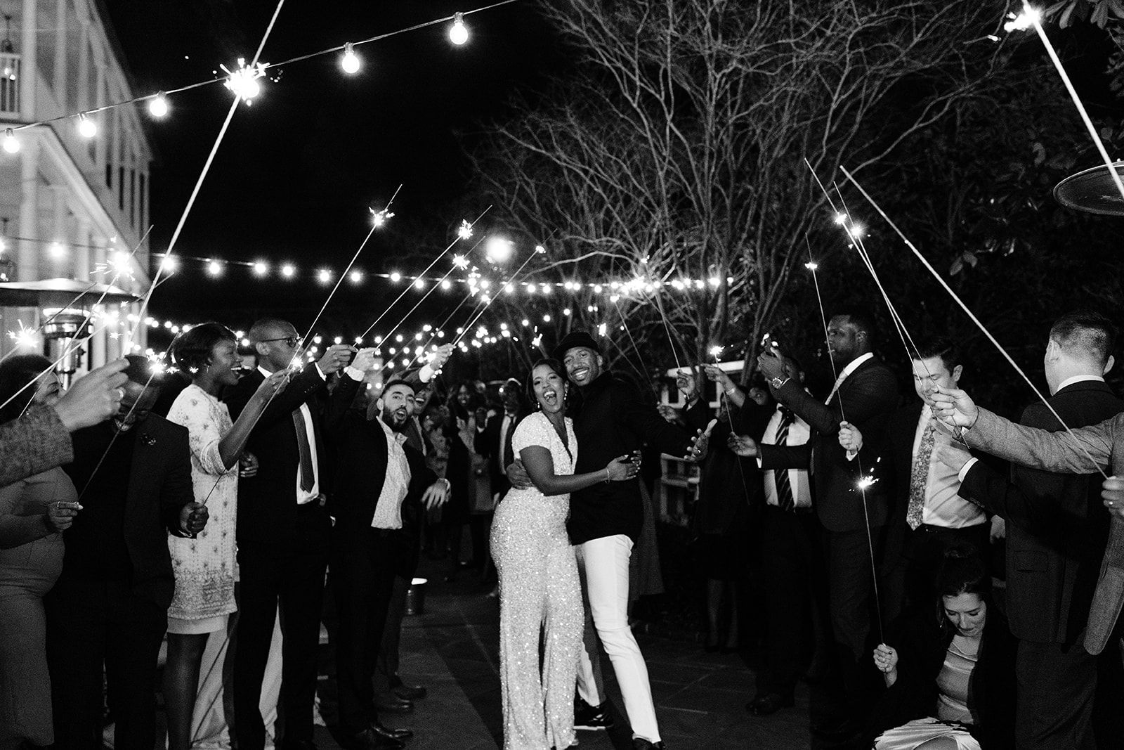 Guests holding sparklers over couple