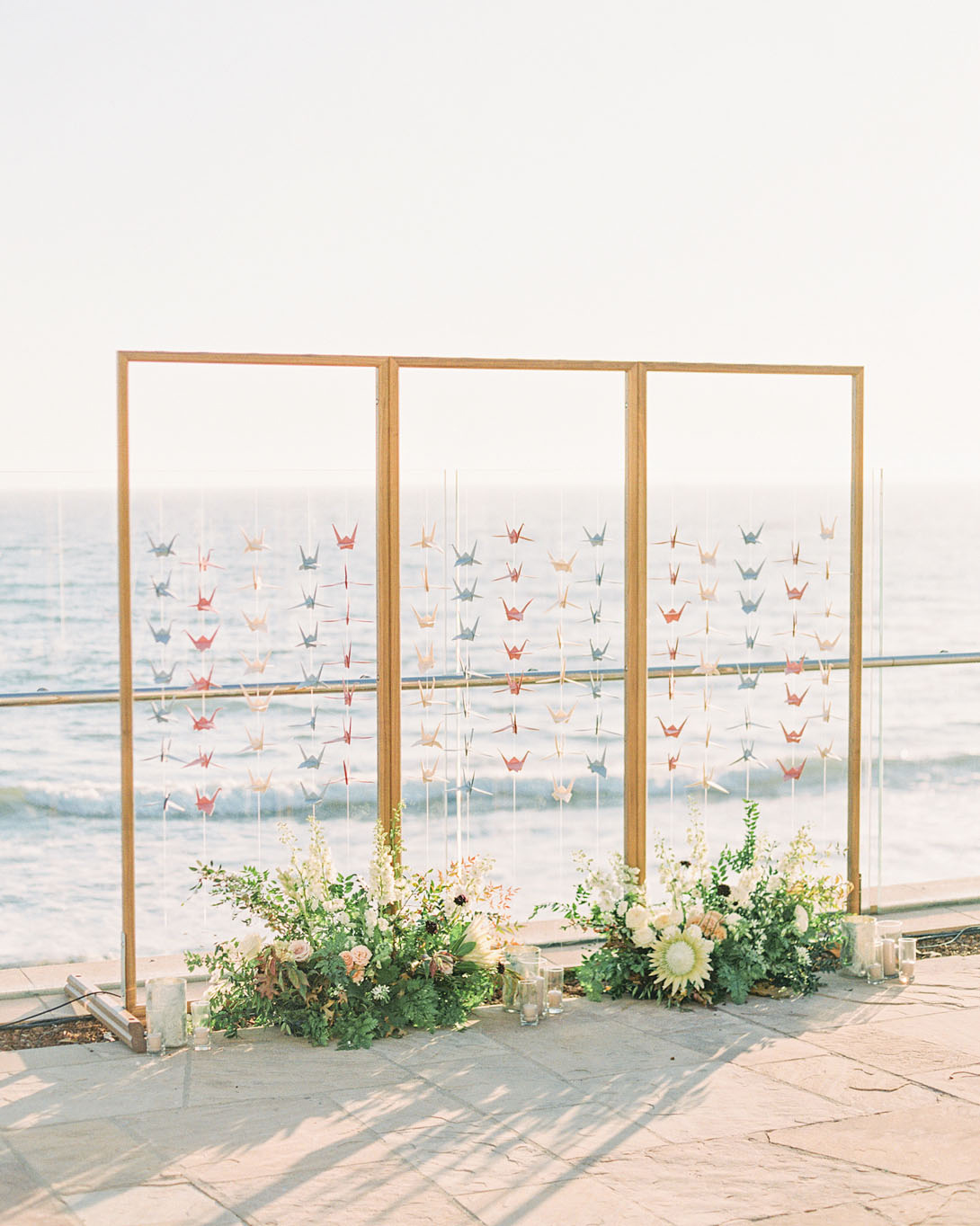 couple origami bird escort cards hanging by ocean