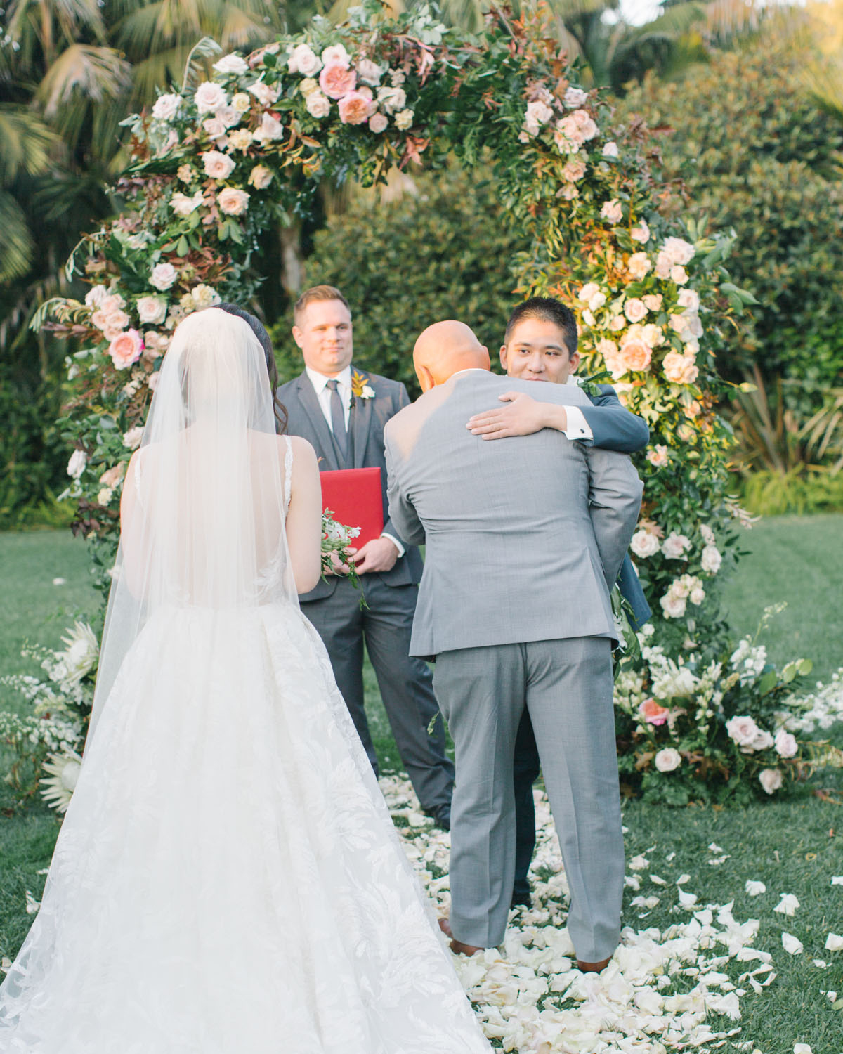 groom hugging father of the bride after processional