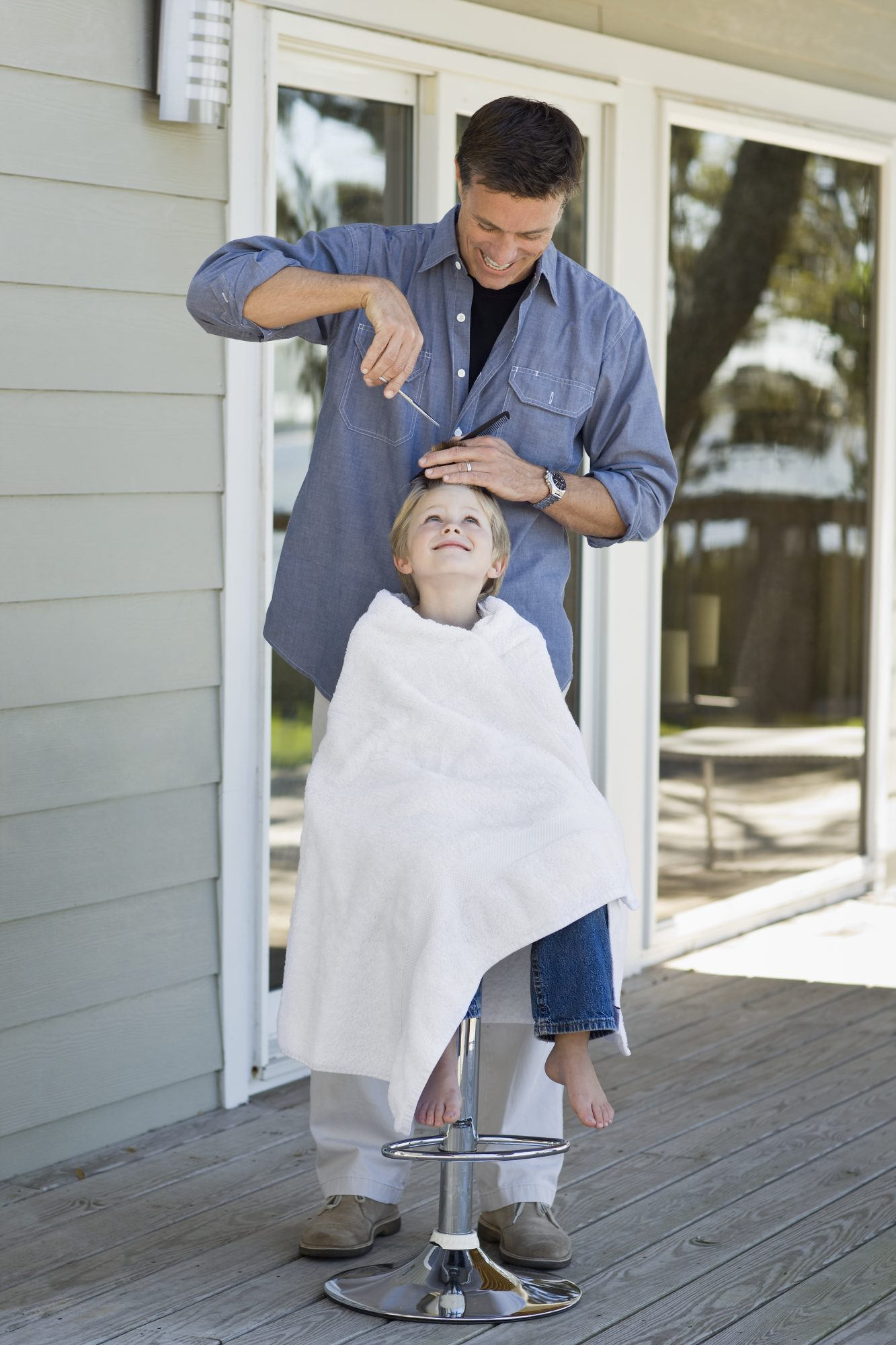 father cutting son's hair outside