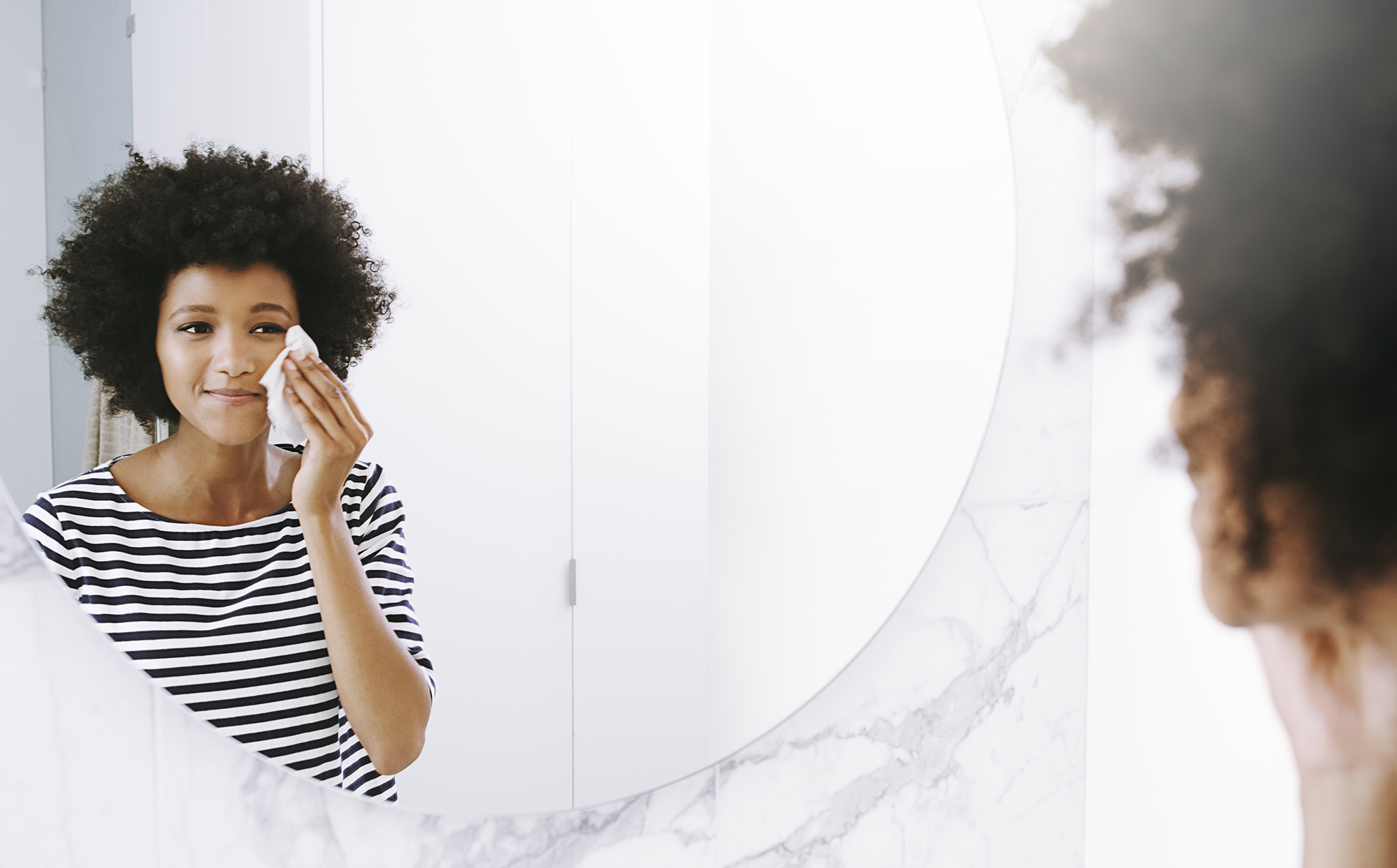 Person looking in mirror and removing makeup