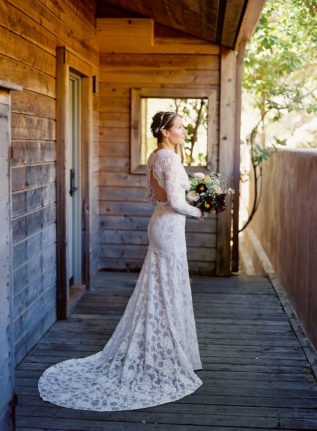 bride in white lace dress standing on rustic porch