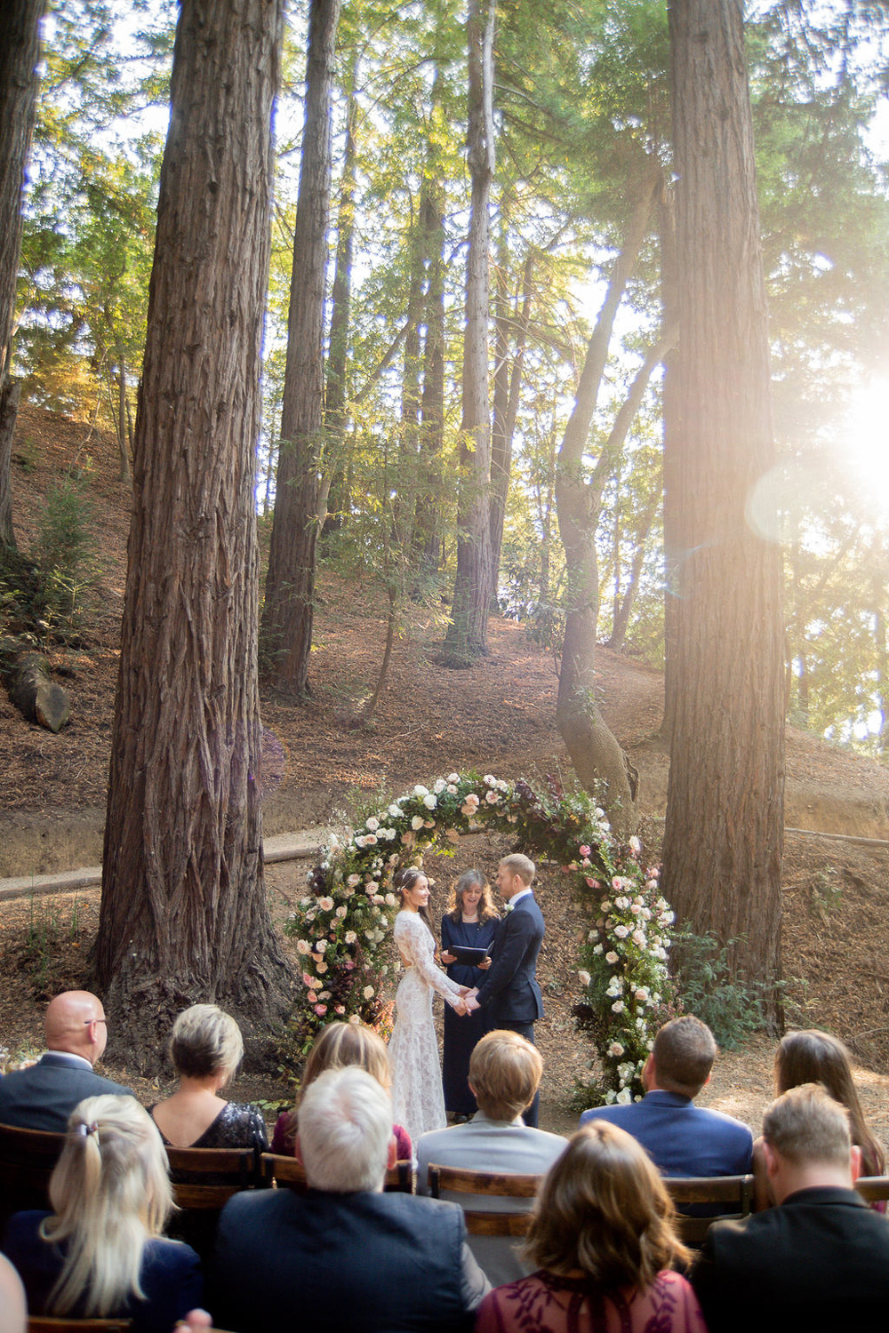 couple holding hands during ceremony under red wood trees
