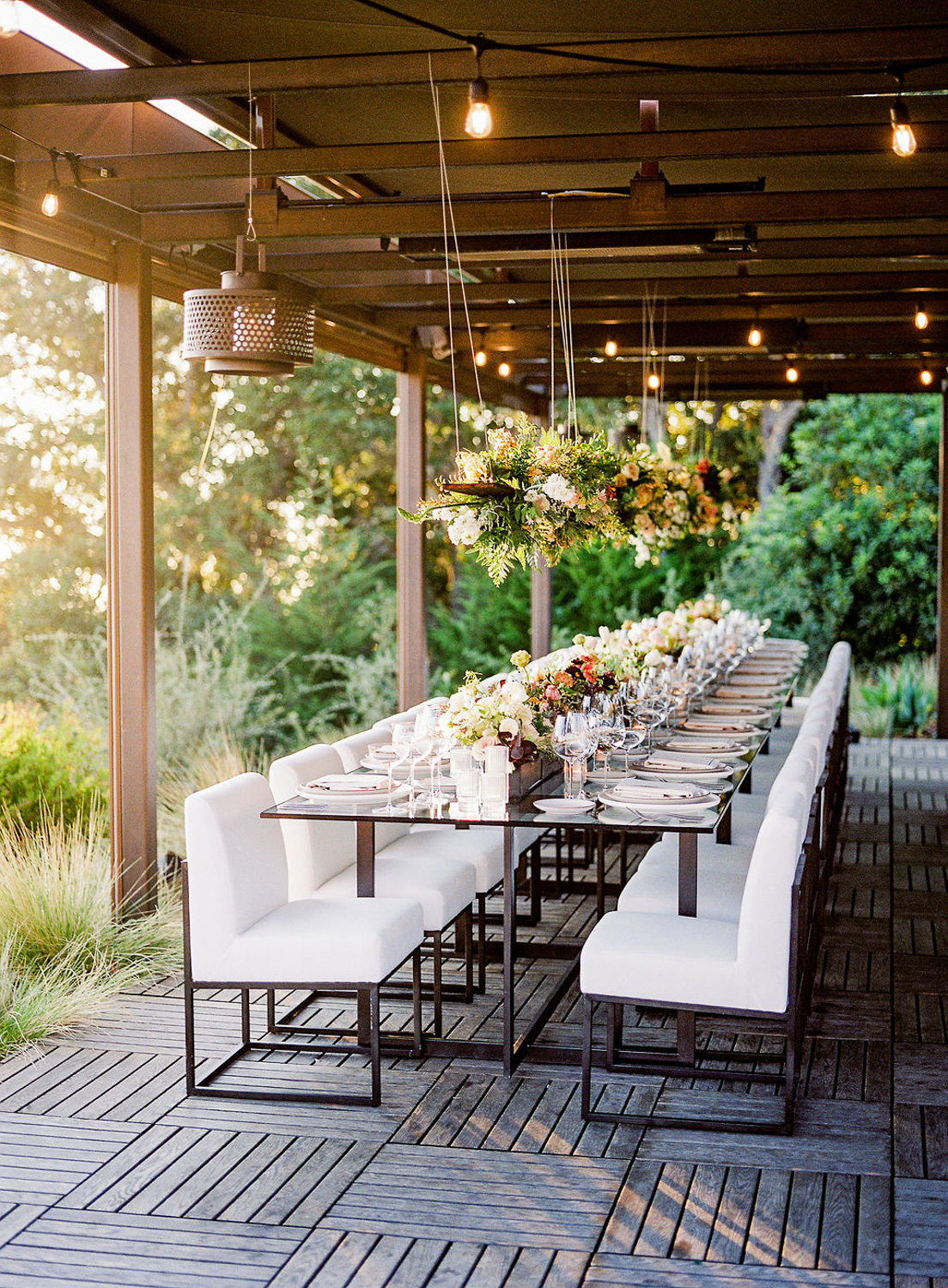 long wedding reception table with white chairs and floral hangings