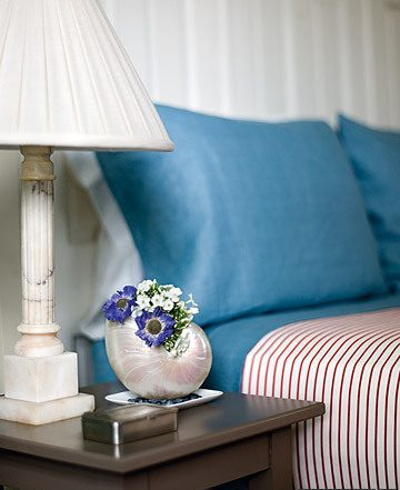 nautilus shell vase next to bed and lamp