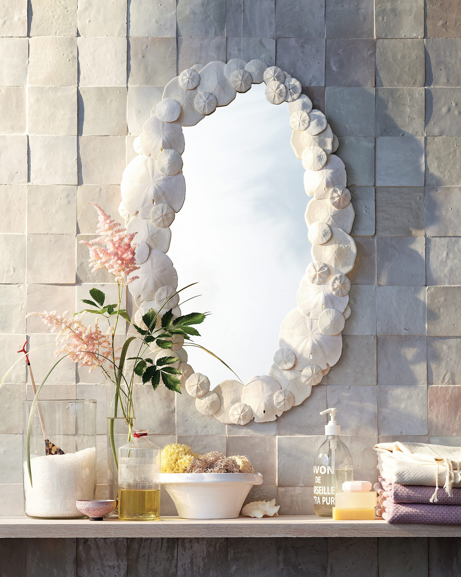sand dollar mirror hanging on wall in bathroom