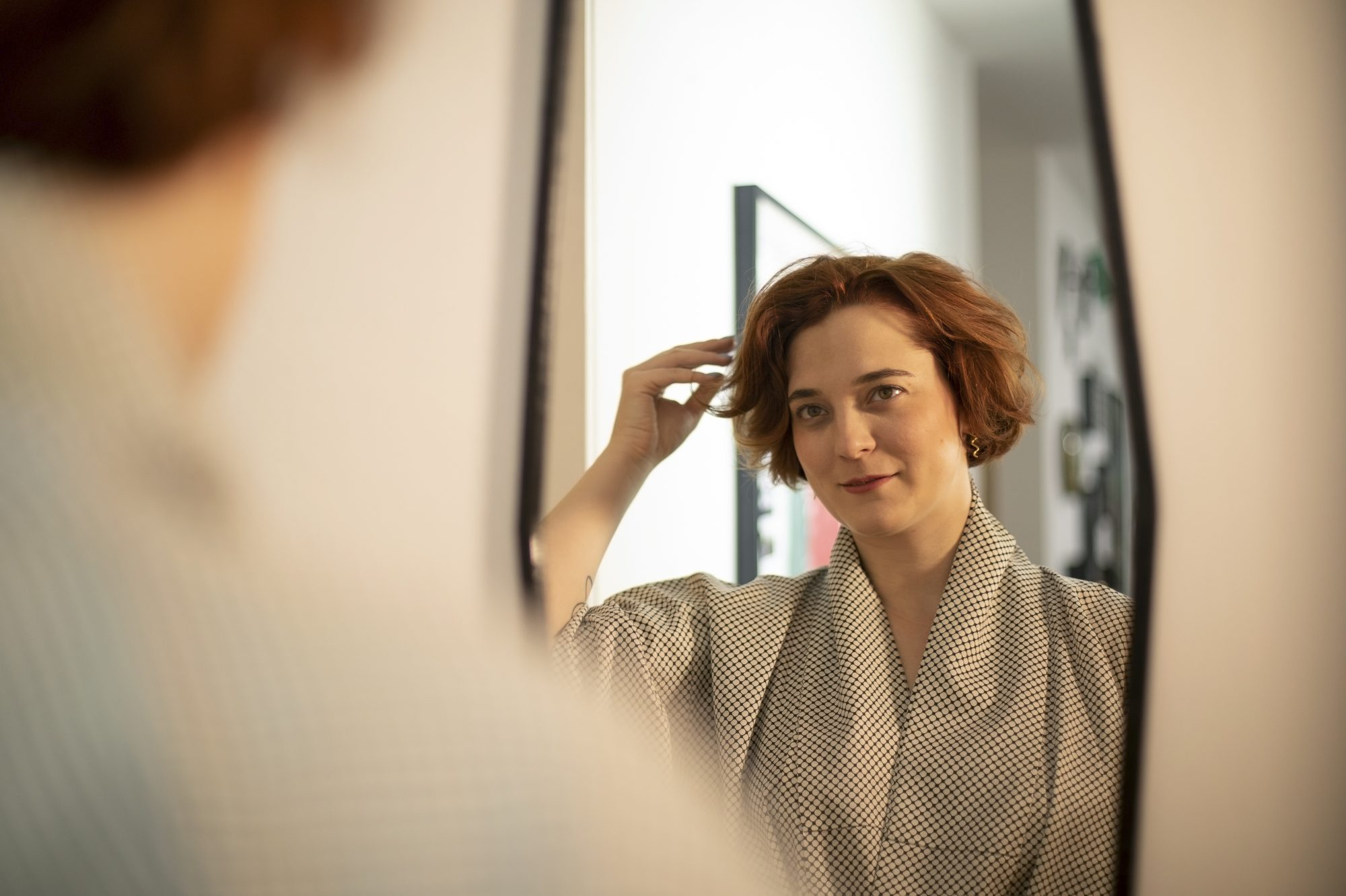 woman touching hair looking in mirror