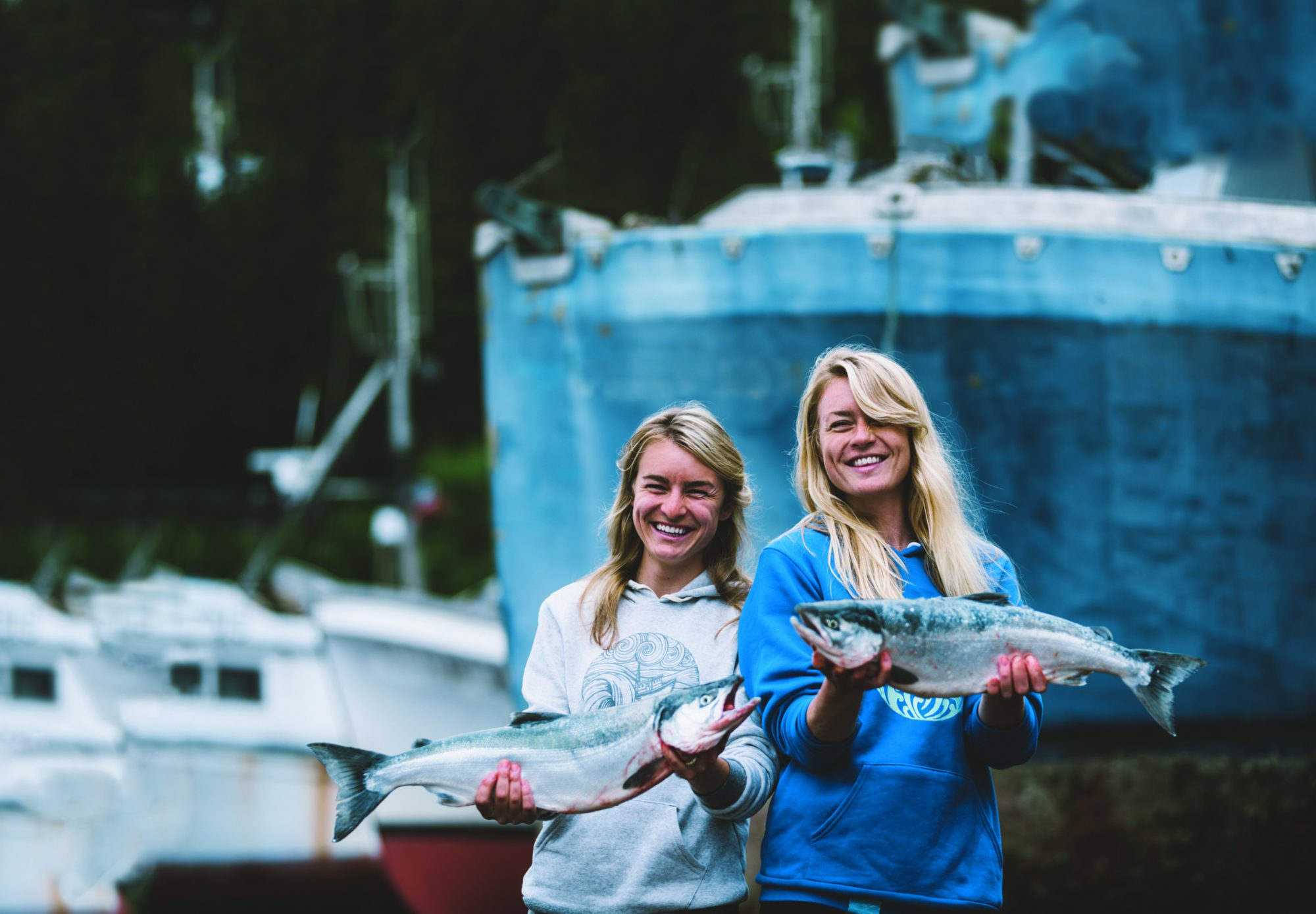 sisters holding salmon beside fishing boat