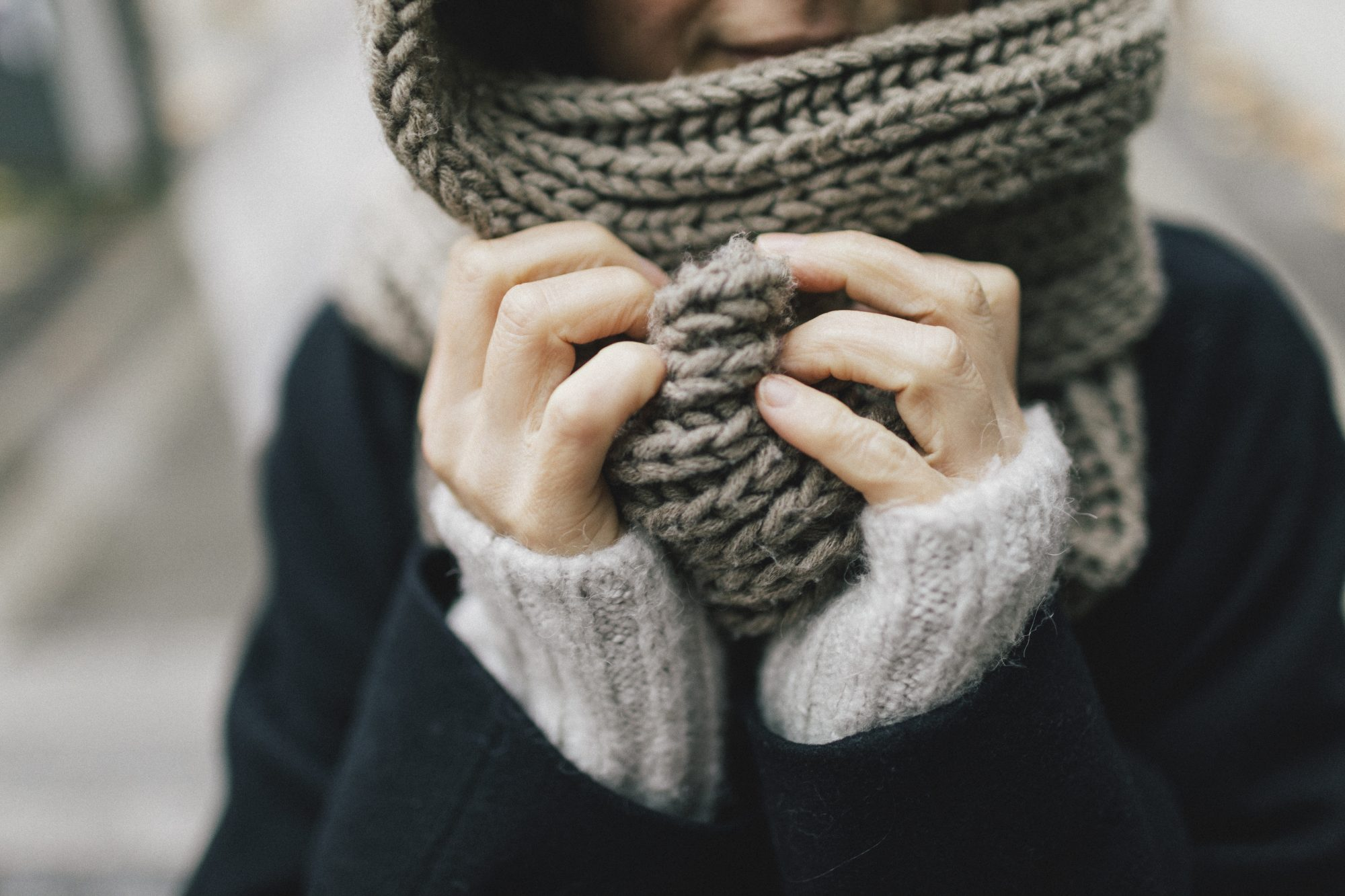 woman's hand holding knitted scarf