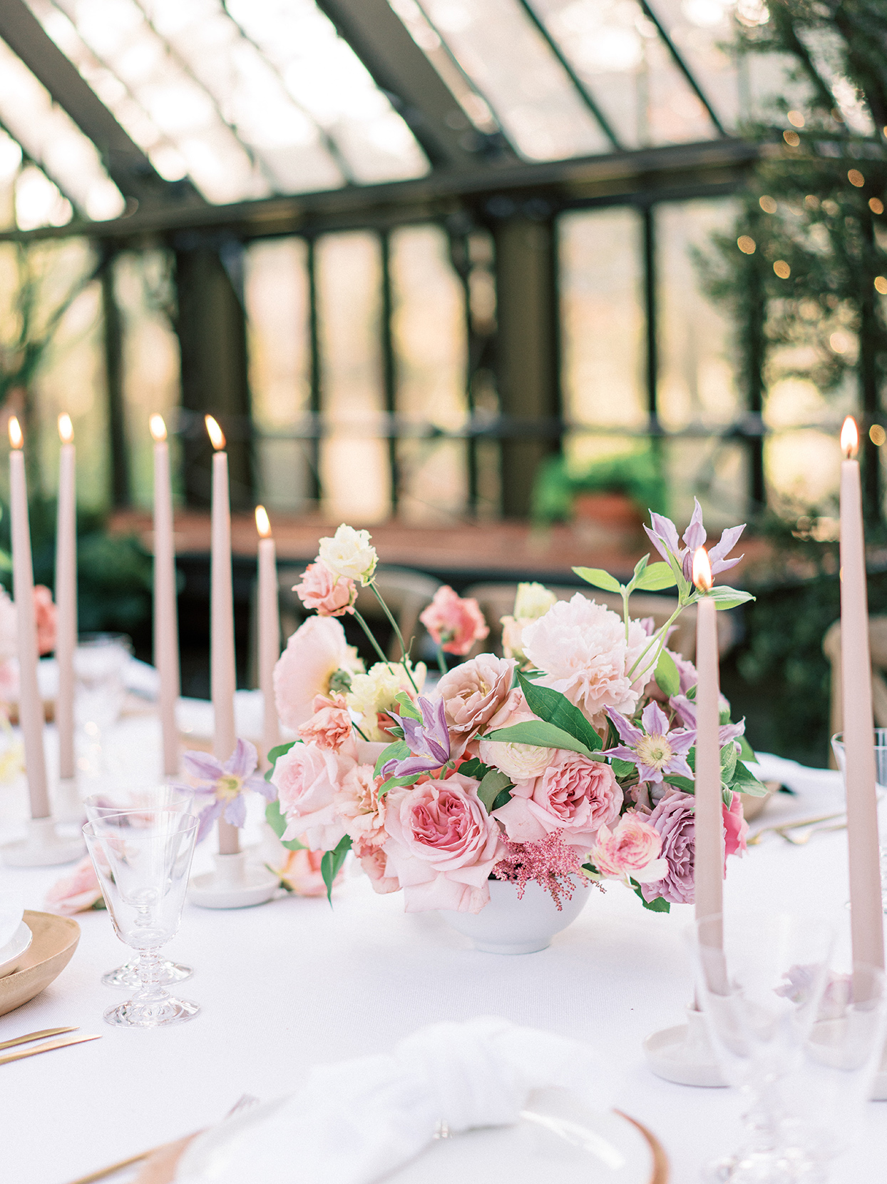 pastel pink and purple wedding centerpiece in greenhouse