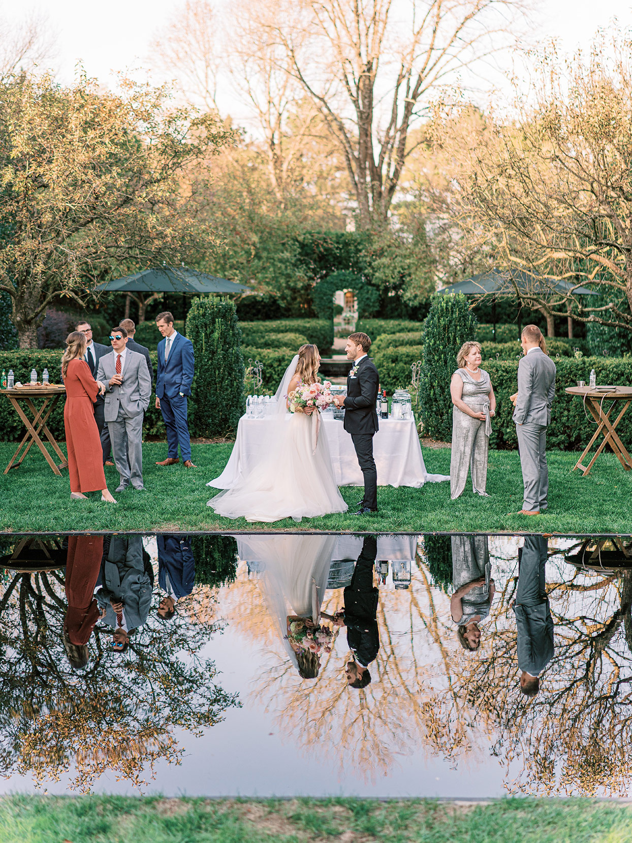 bride and groom during cocktail house with reflection in pond