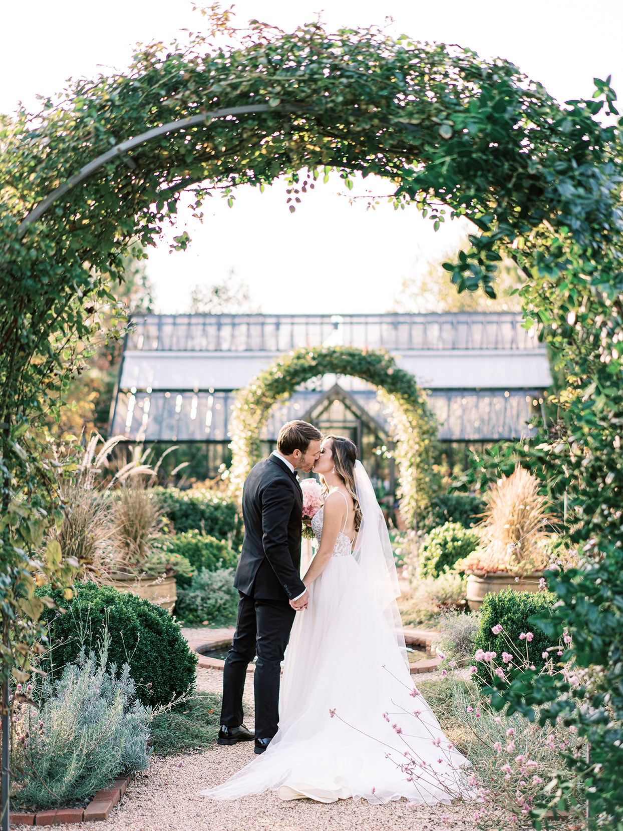 wedding couple kissing under floral arch in garden