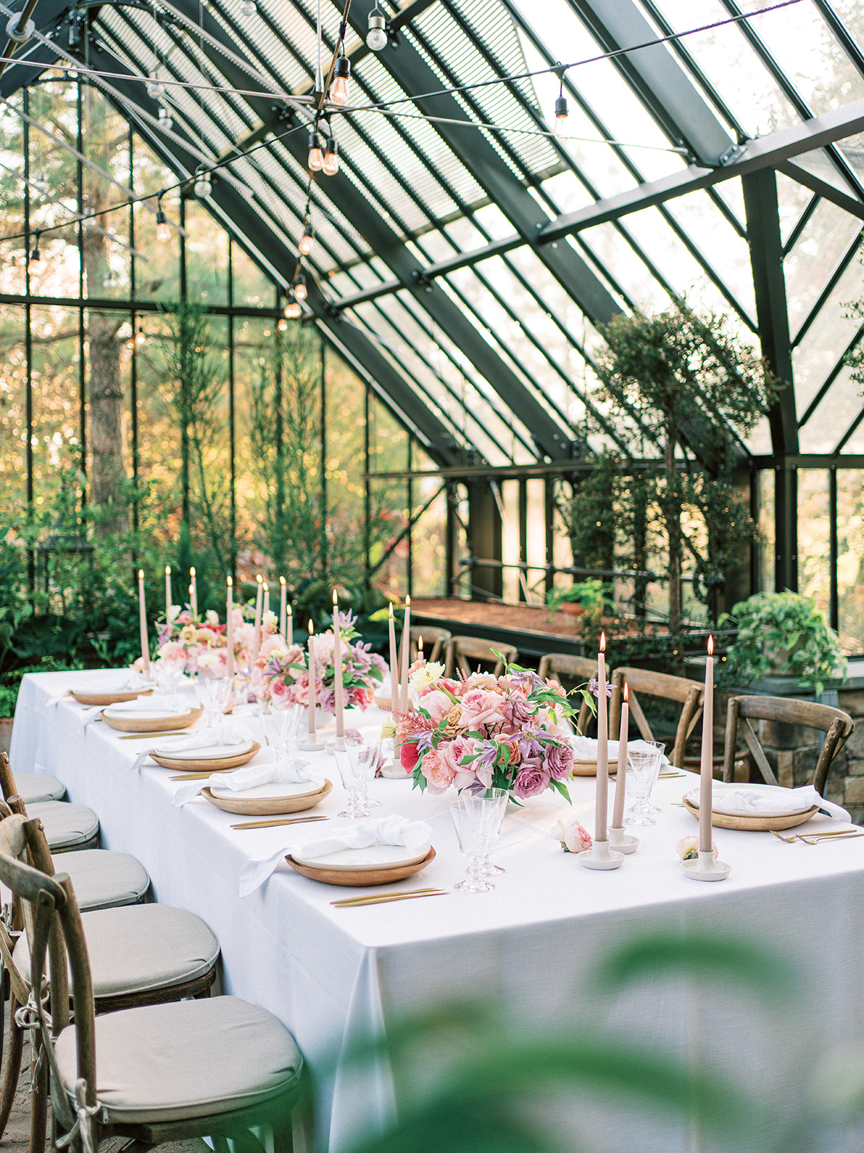 small reception table with pink and purple floral centerpieces in greenhouse