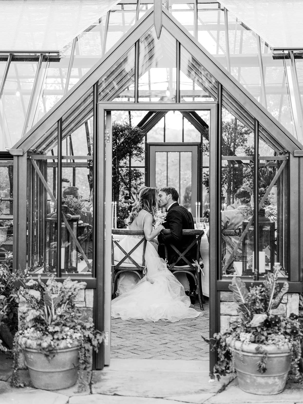 wedding reception couple kissing in greenhouse
