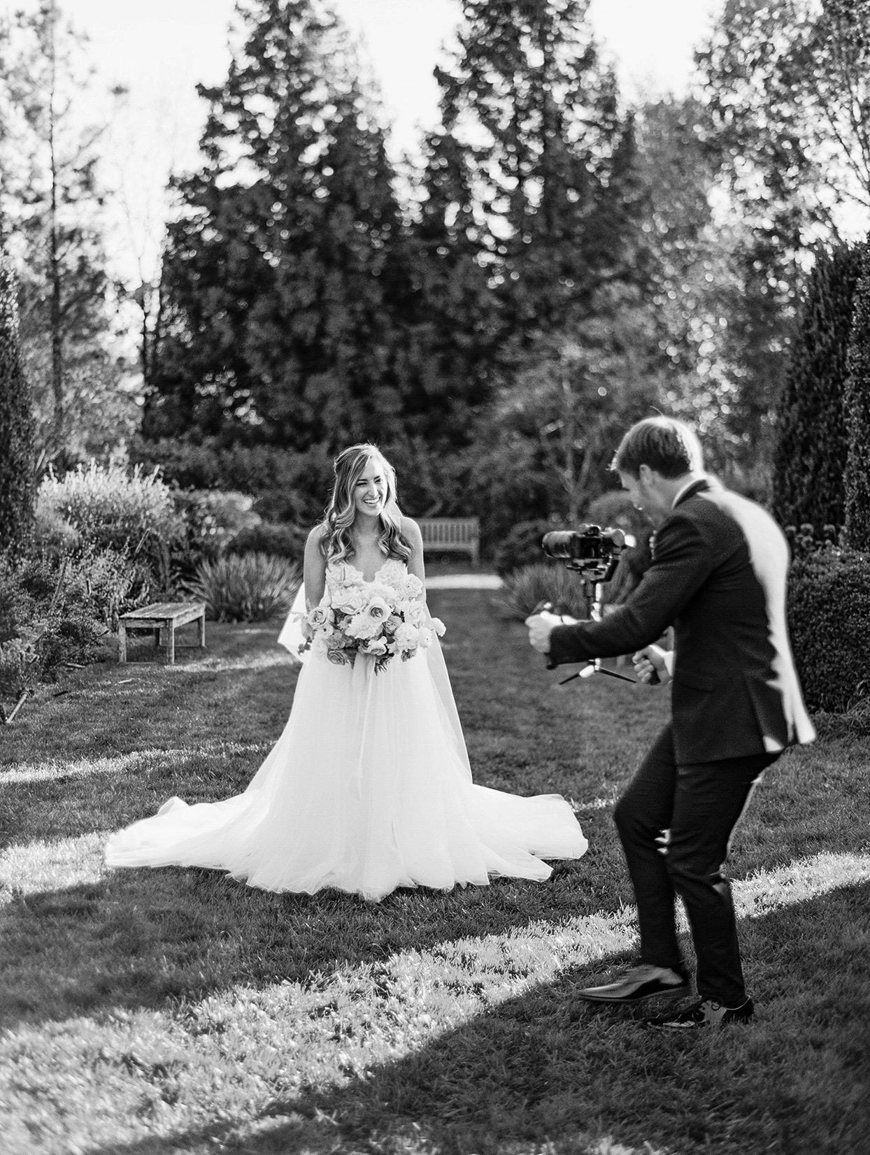 groom filming bride in garden while both are laughing