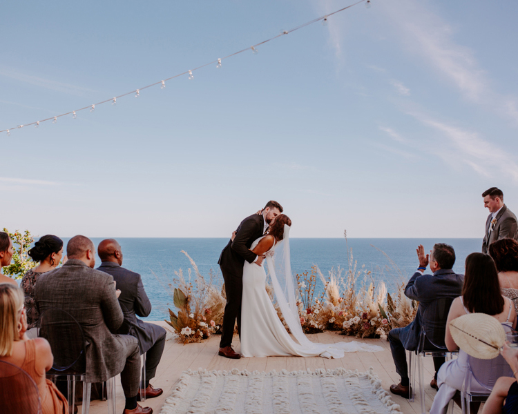 wedding couple kissing at ceremony with ocean view