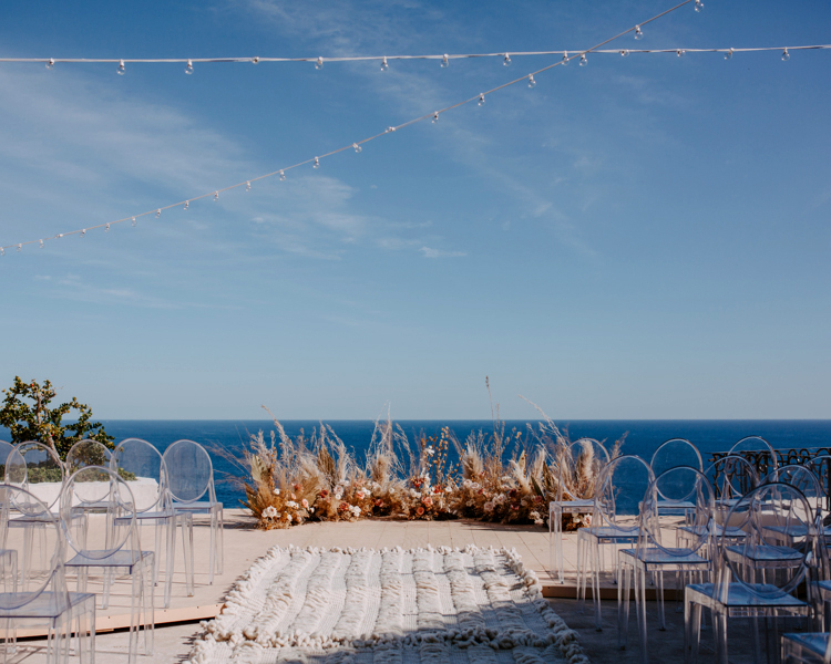 modern bohemian wedding ceremony set up with clear chairs and ocean view