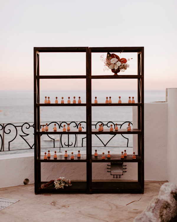 wedding escort card vials displayed on black shelf overlooking water