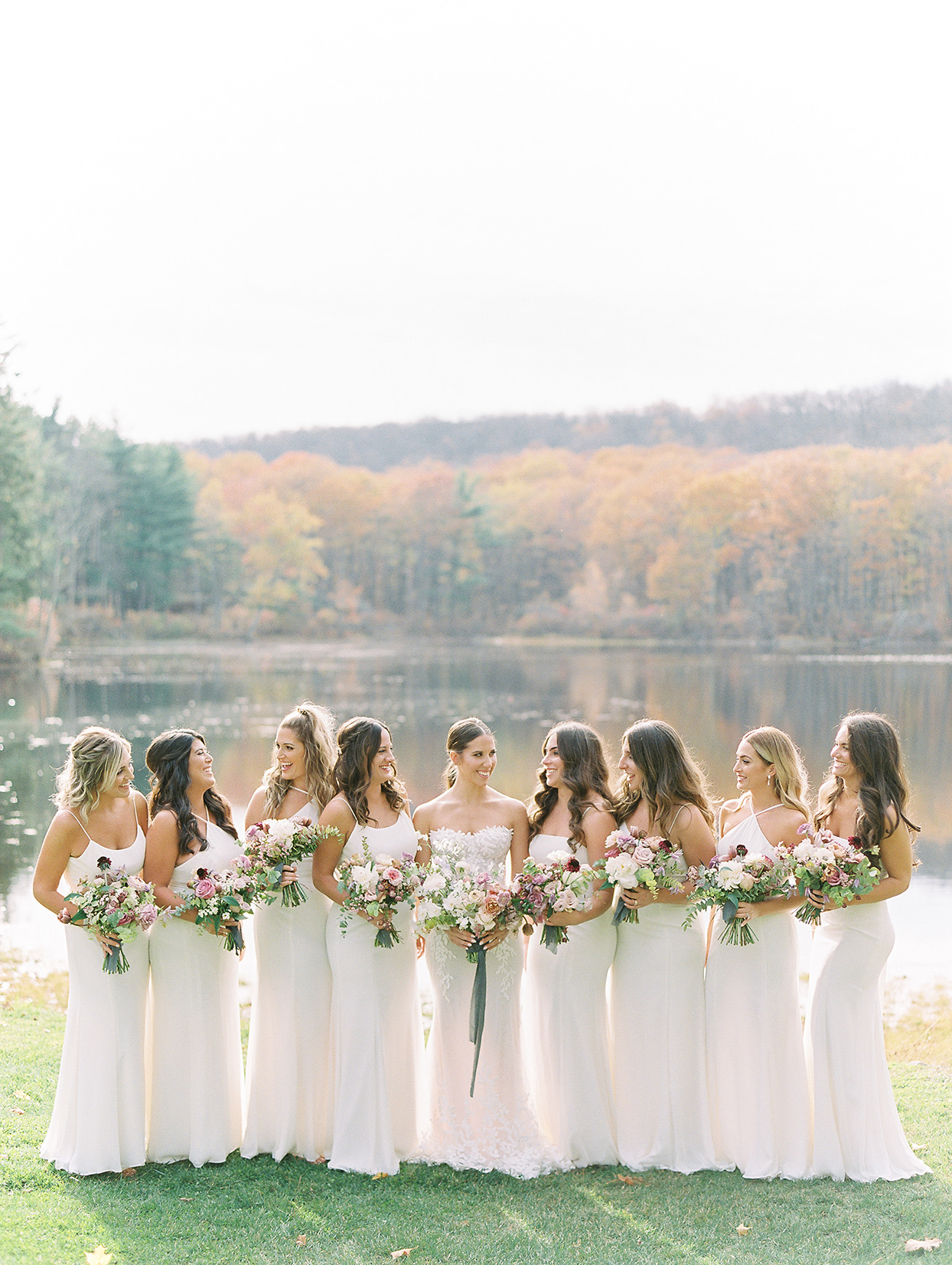 bridesmaids in white with bride standing by water