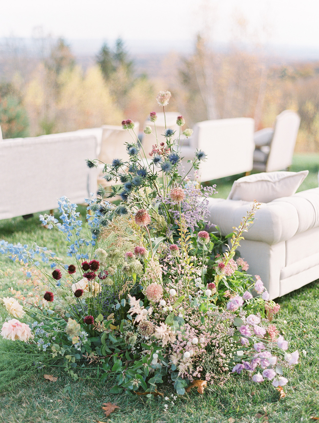 large floral display next to white ceremony couches