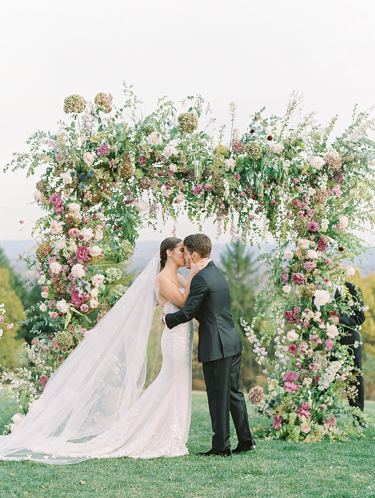 wedding couple kissing under floral arch
