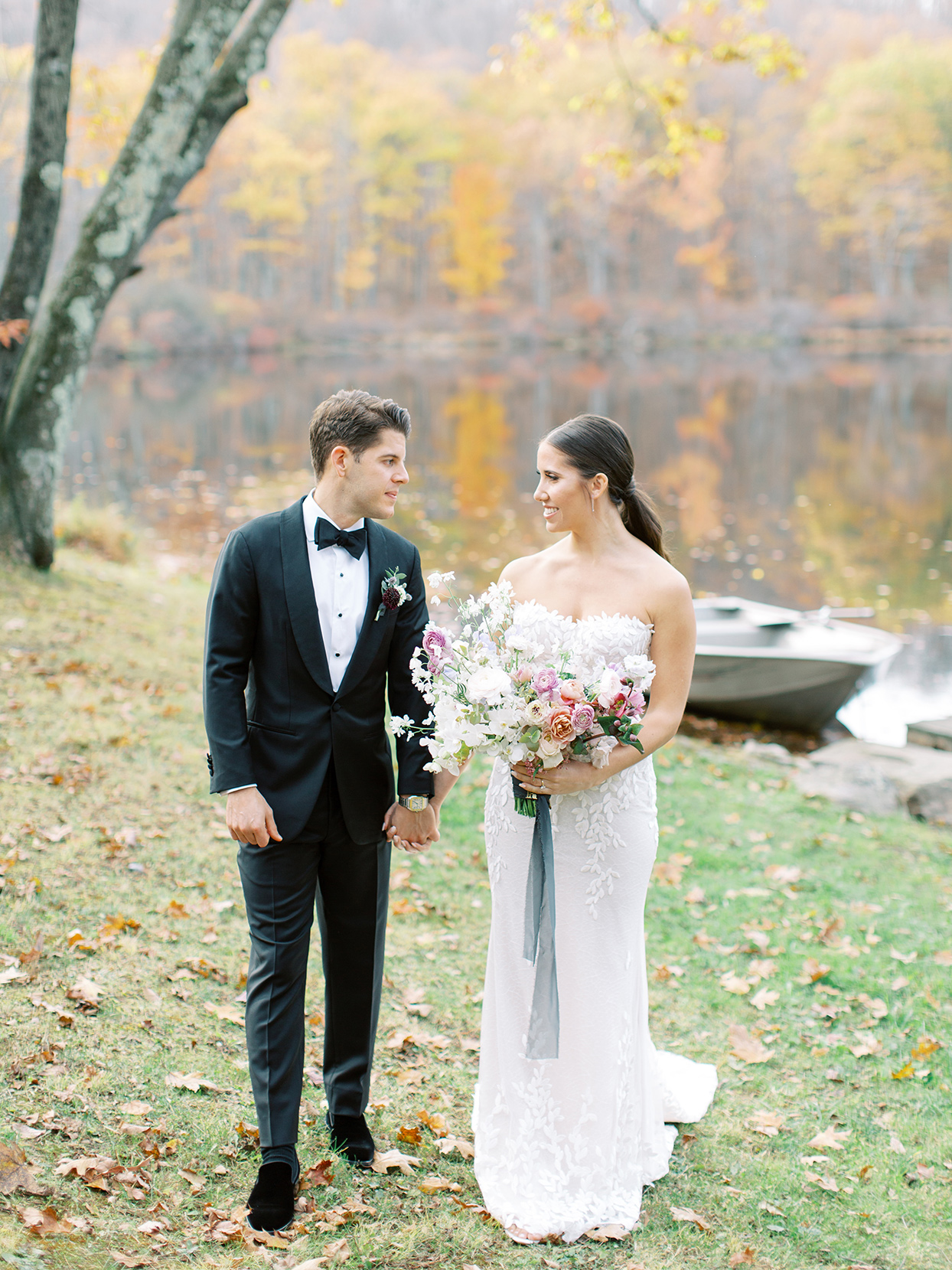 wedding couple holding hands by lake